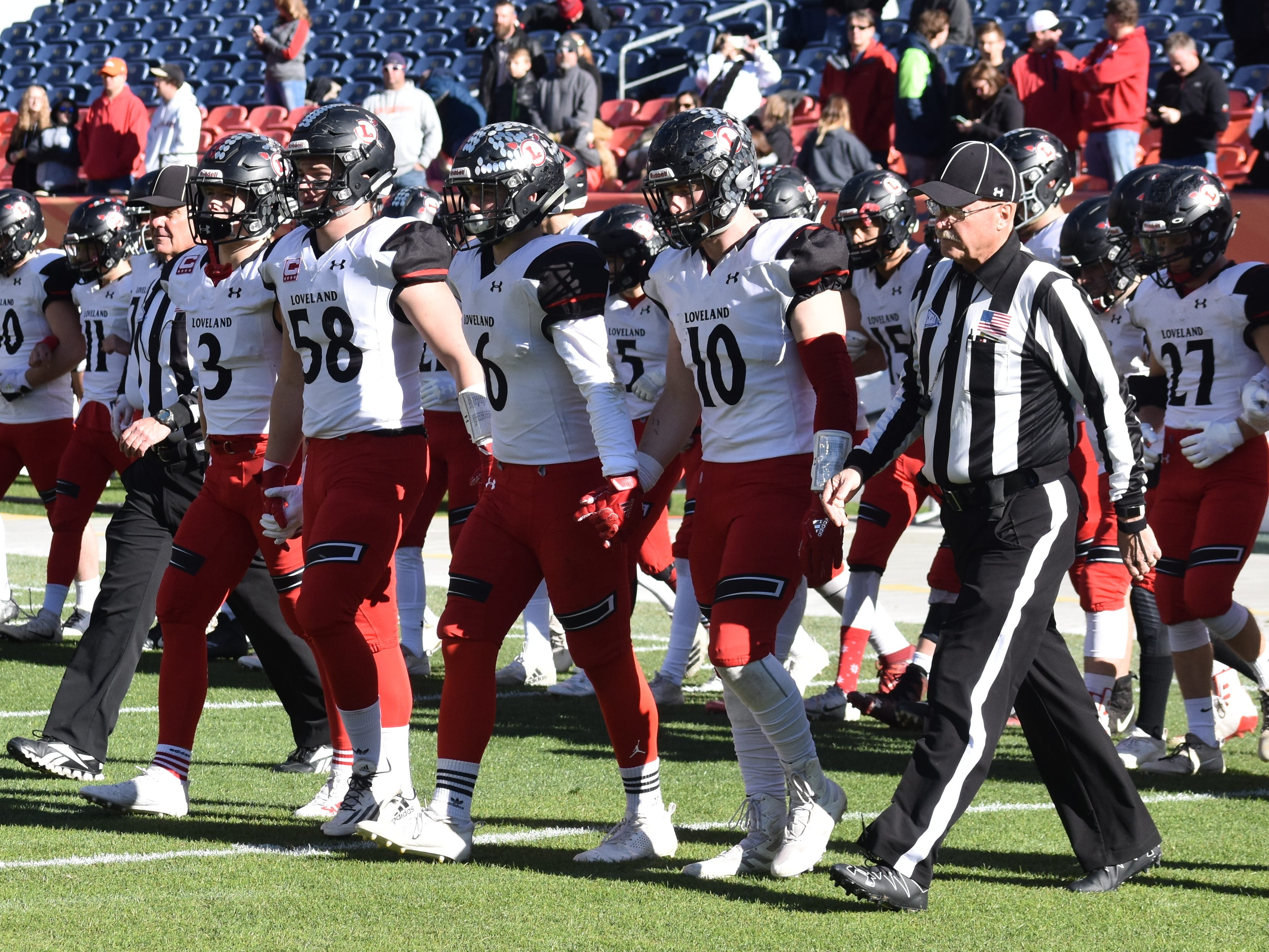 Loveland High football team captains Zach Weinmaster, Michael Deschene, Colby Mauck and Sean Boylan head toward midfield with the officials for the coin toss before Saturday's Class 4A state title game in Denver.