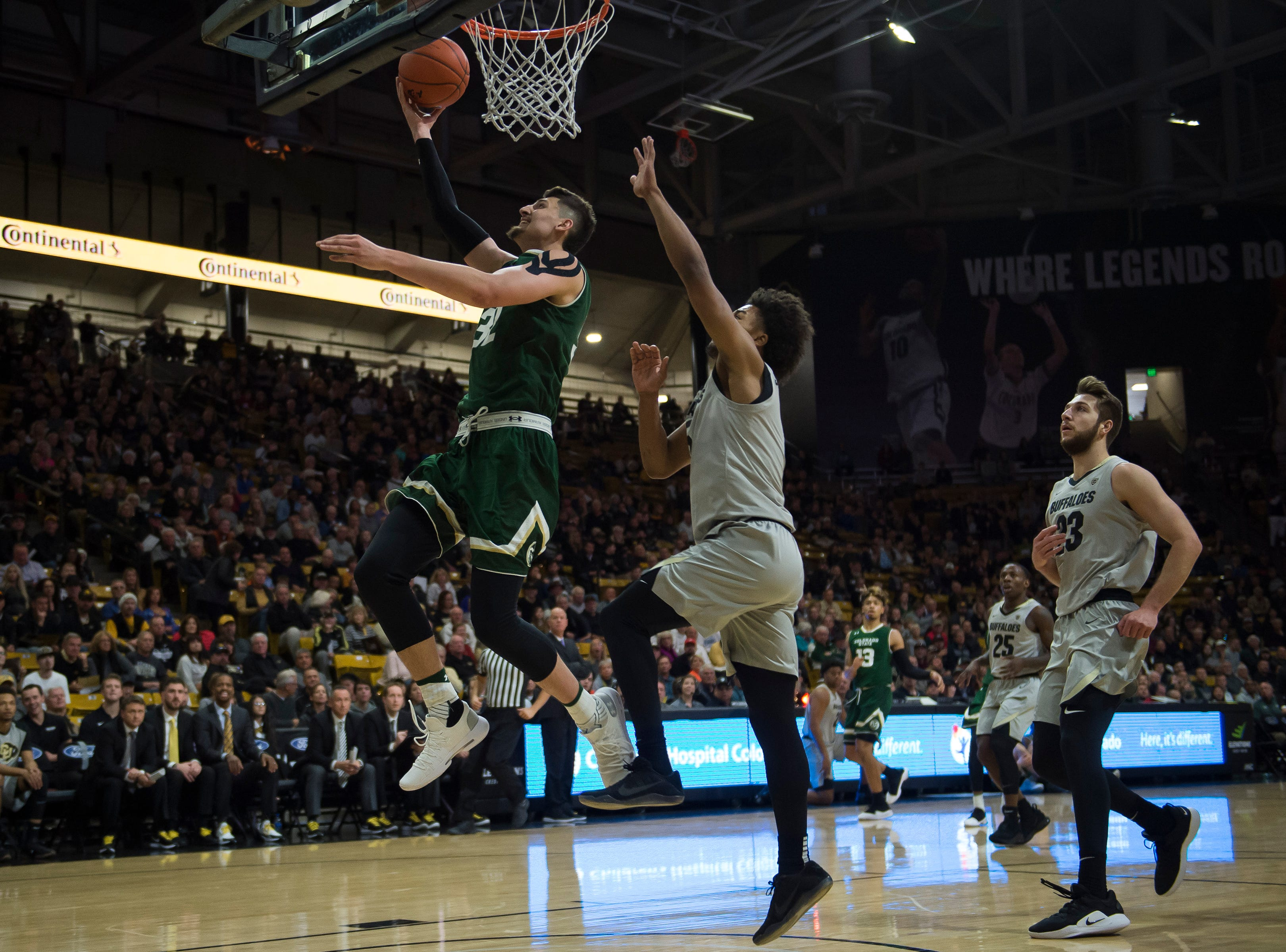 Colorado State University junior center Nico Carvacho (32) goes for a layup past University of Colorado sophomore guard D'Shawn Schwartz (5) on Saturday, Dec. 1, 2018, at the CU Event Center in Boulder, Colo.