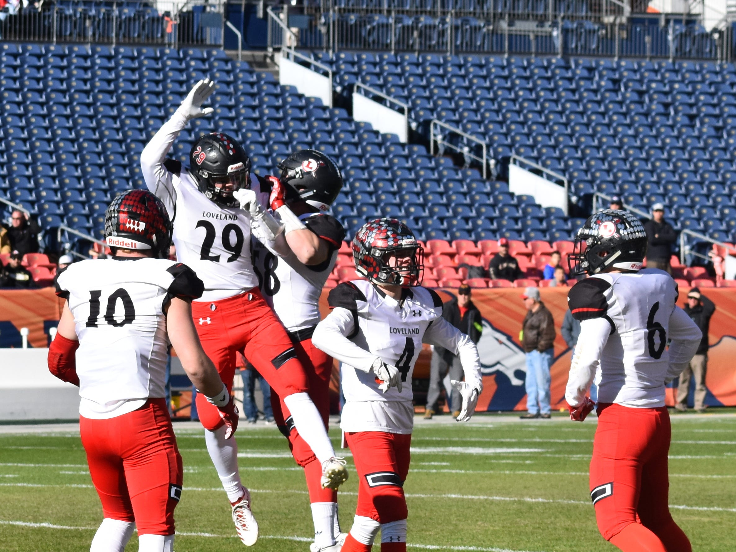 Loveland High football player Michael Lewis celebrates a big play with teammates during Saturday's Class 4A state championship game in Denver.