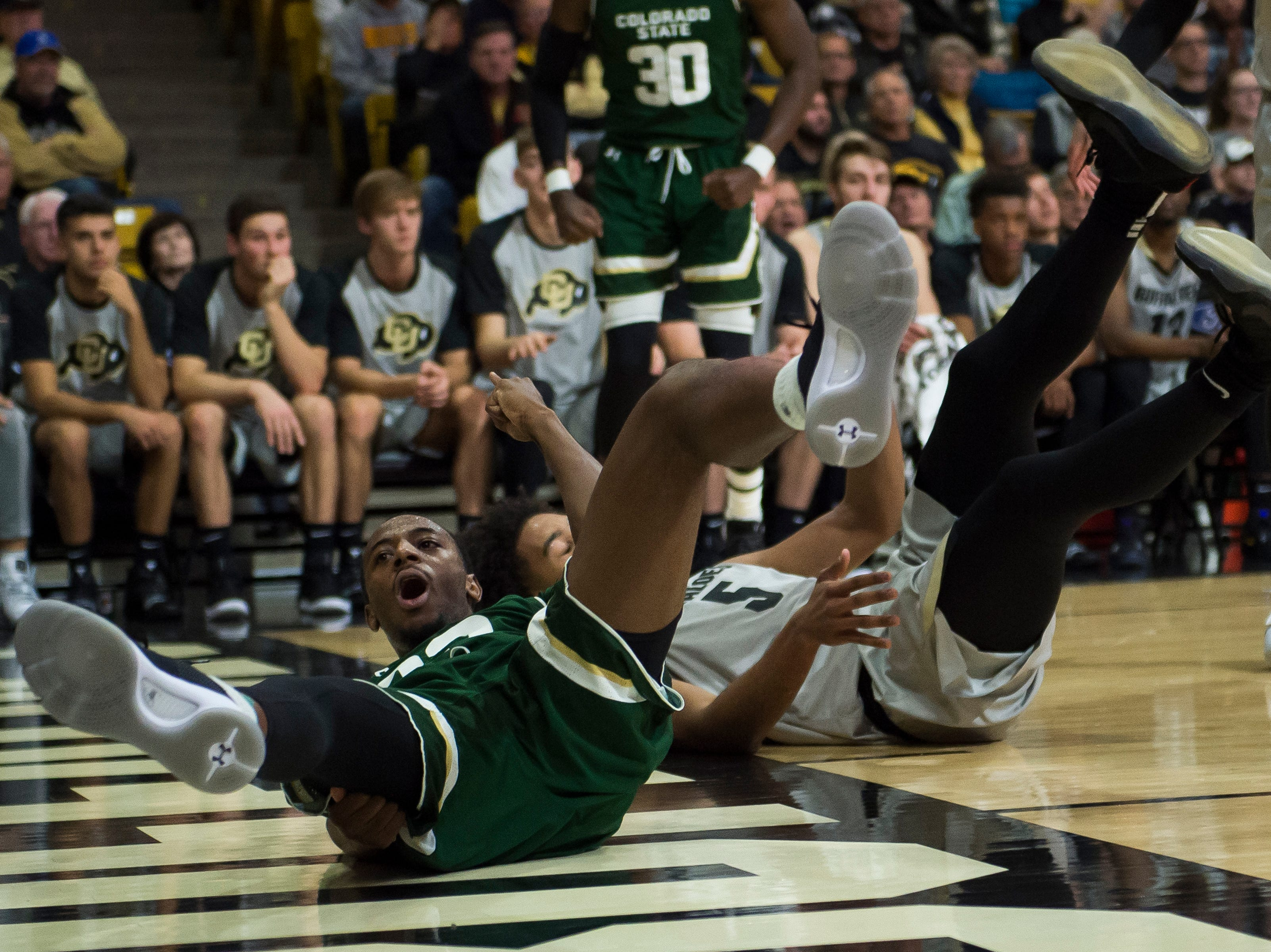 Colorado State University senior guar J.D. Paige (22) yells as he falls to the floor after being fouled by University of Colorado sophomore guard D'Shawn Schwartz (5) on Saturday, Dec. 1, 2018, at the CU Event Center in Boulder, Colo.