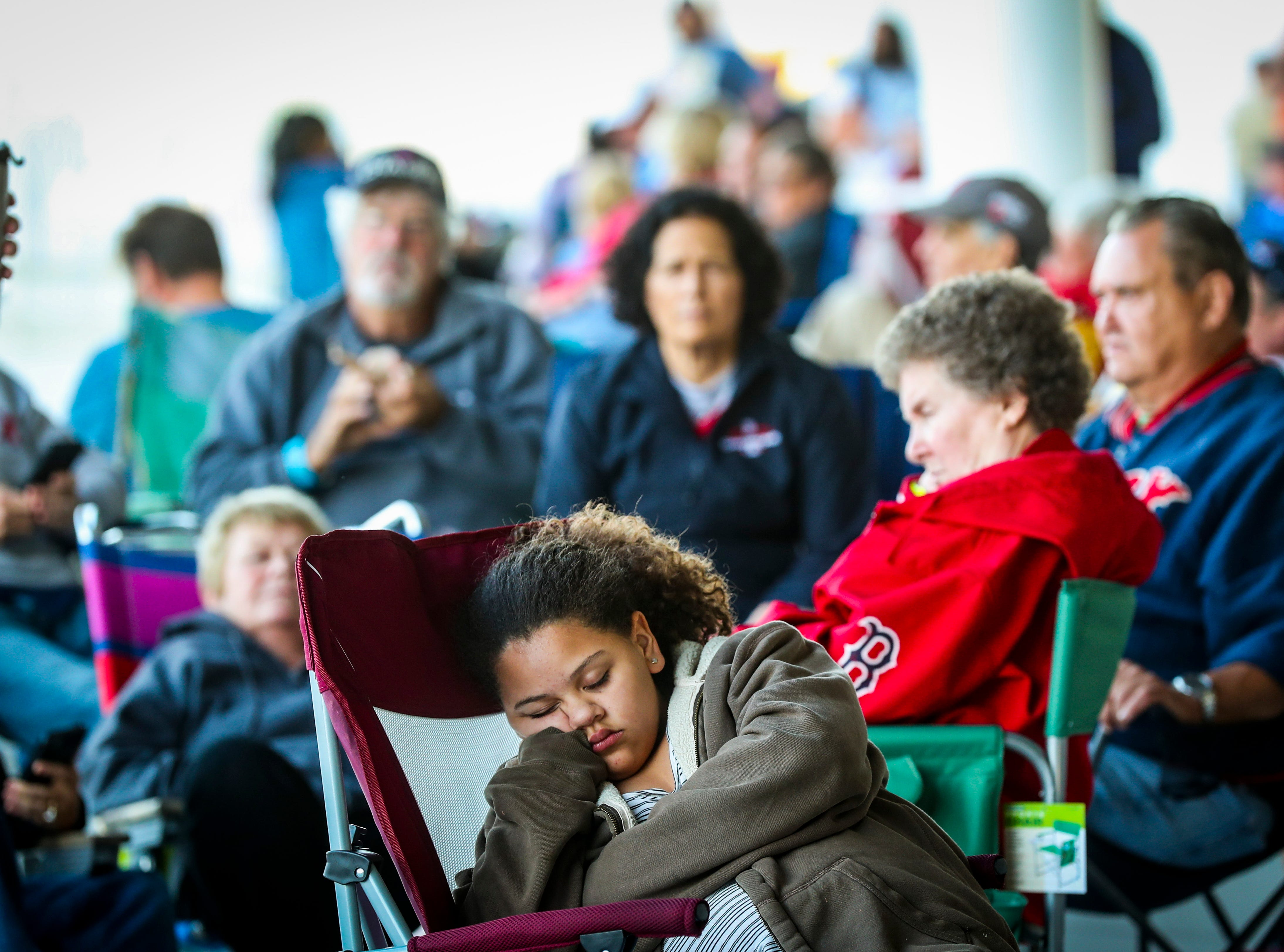 Jayliene Negron, 15 of Lehigh, snoozes in the early hours as she waits for the chance to buy Red Sox tickets with her family. Boston fans gathered in line for spring training tickets. The crowd is excited for this season after the Red Sox won the World Series.