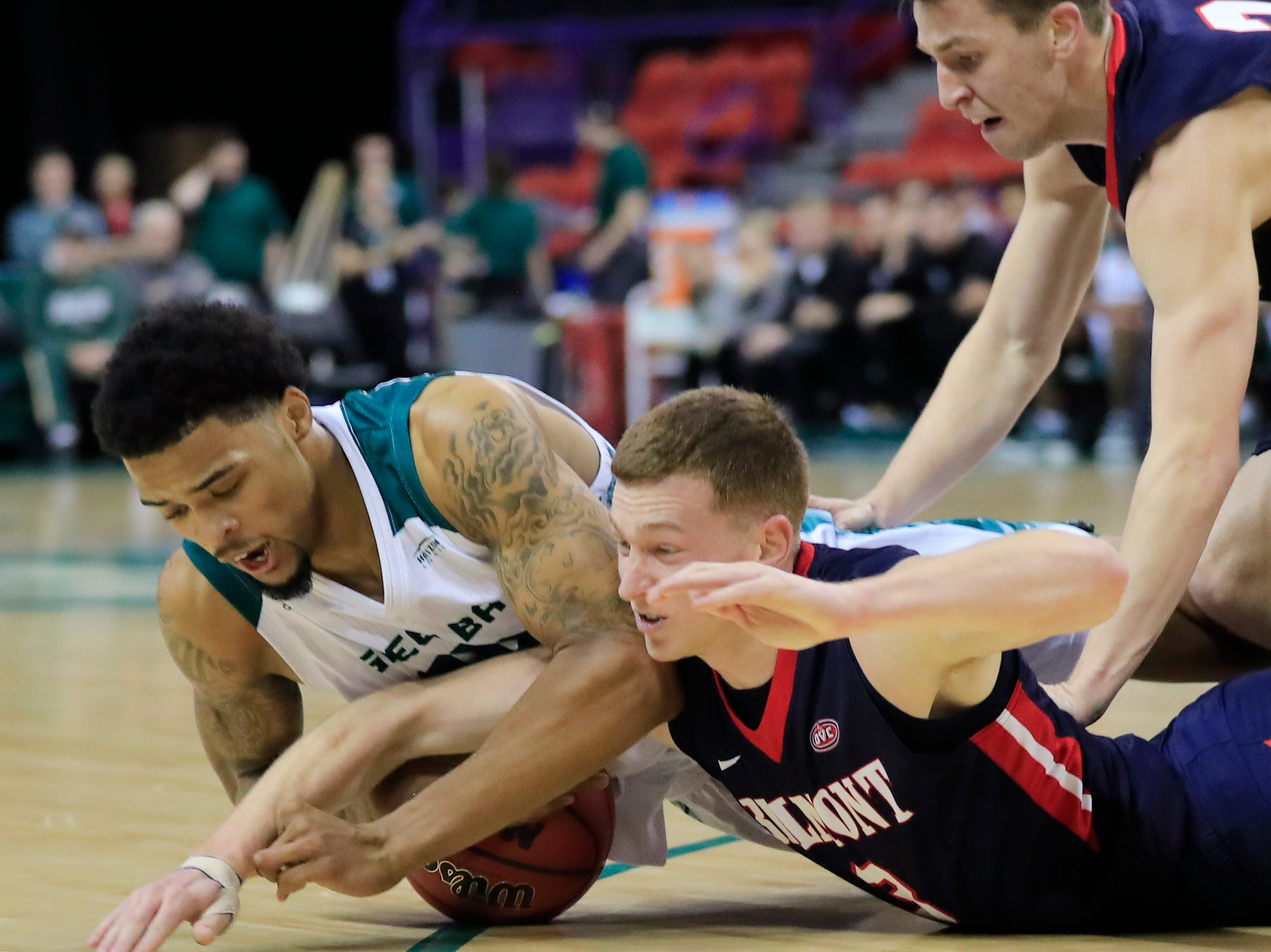 Green Bay Phoenix forward Manny Patterson (15) and Belmont Bruins guard Dylan Windler (3) dive for a loose ball in a NCAA basketball game at the Resch Center on Saturday, December 1, 2018 in Ashwaubenon, Wis.
