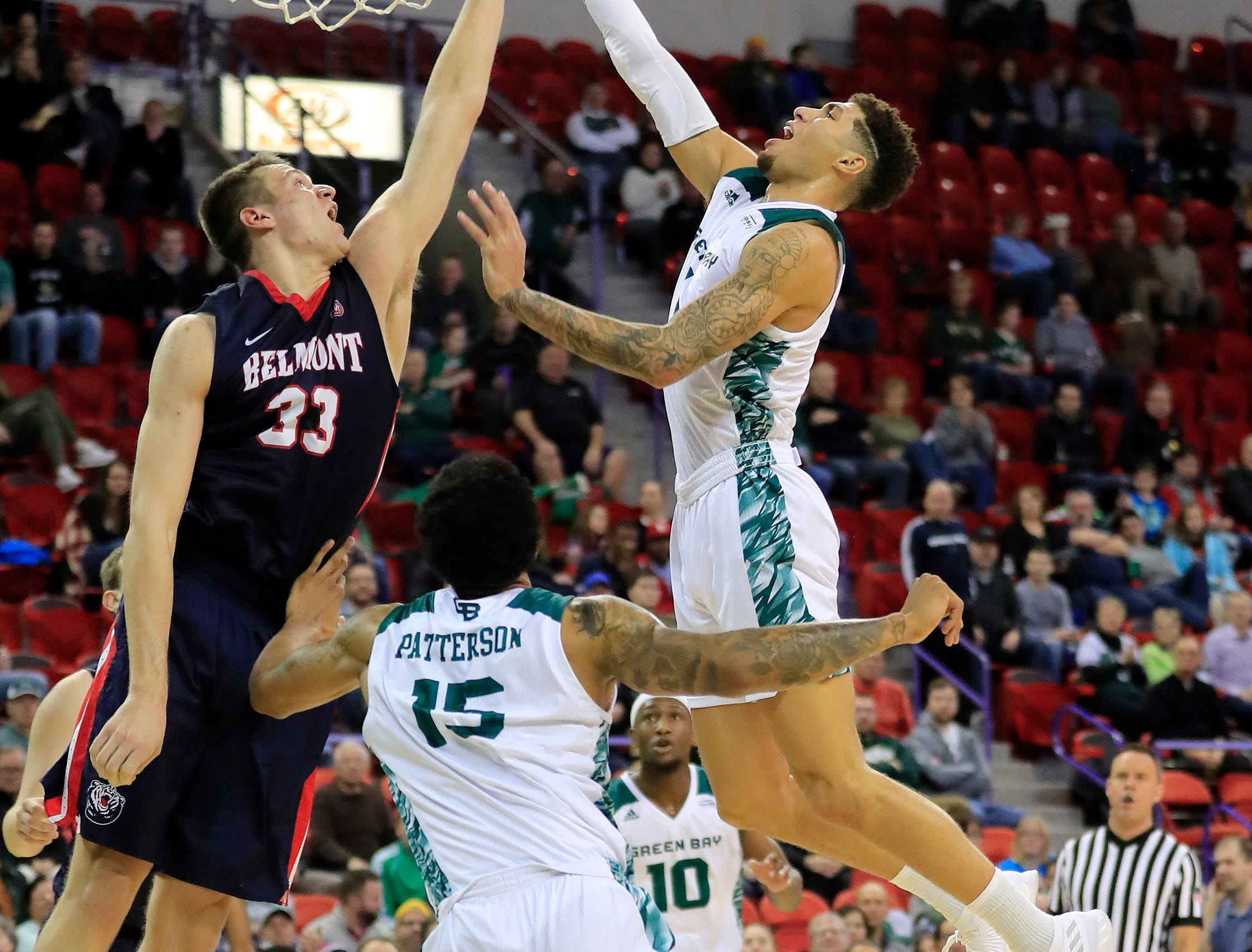 Green Bay Phoenix guard Sandy Cohen III (1) draws a foul on Belmont Bruins center Nick Muszynski (33) in a NCAA basketball game at the Resch Center on Saturday, December 1, 2018 in Ashwaubenon, Wis.