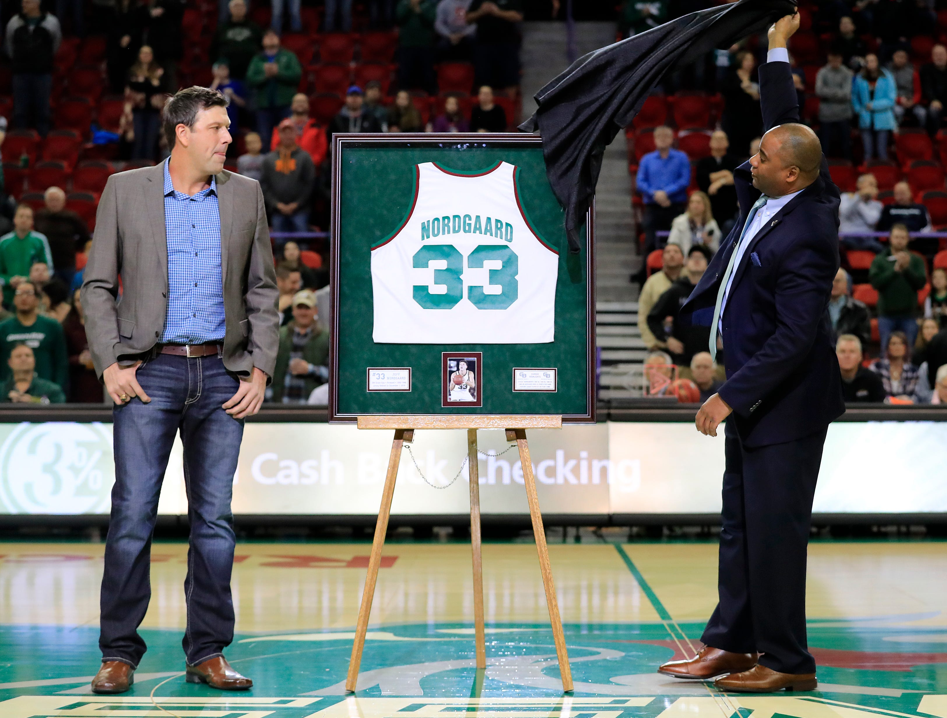 Athletics Director Charles Guthrie presents former UW-Green Bay basketball player Jeff Nordgaard a framed jersey during halftime of a NCAA basketball game at the Resch Center on Saturday, December 1, 2018 in Ashwaubenon, Wis.