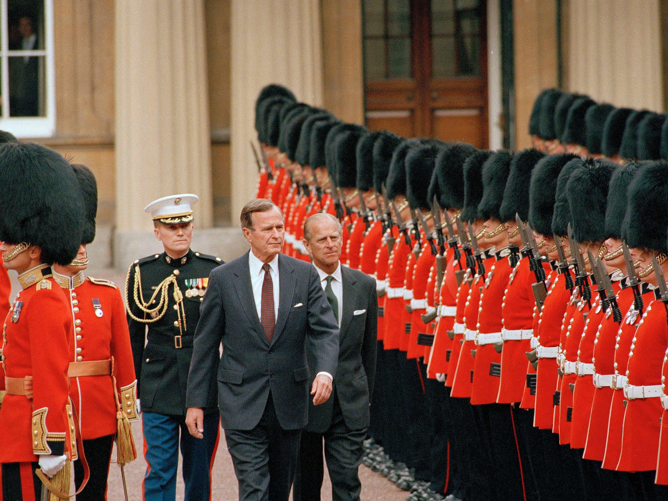 President George Bush and Prince Philip review a line of honor of the Scots Guards in the quadrangle of Buckingham Palace in London, June 1, 1989. (AP Photo/Dennis Cook)