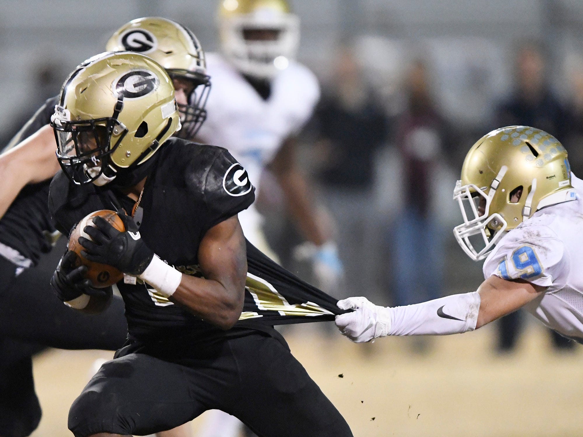 Daniel's Jacob Hendricks (19) hangs on to Greer's Dre Williams (22) in the class AAAA upstate championship Friday, November 30, 2018 at Greer's Dooley Field.