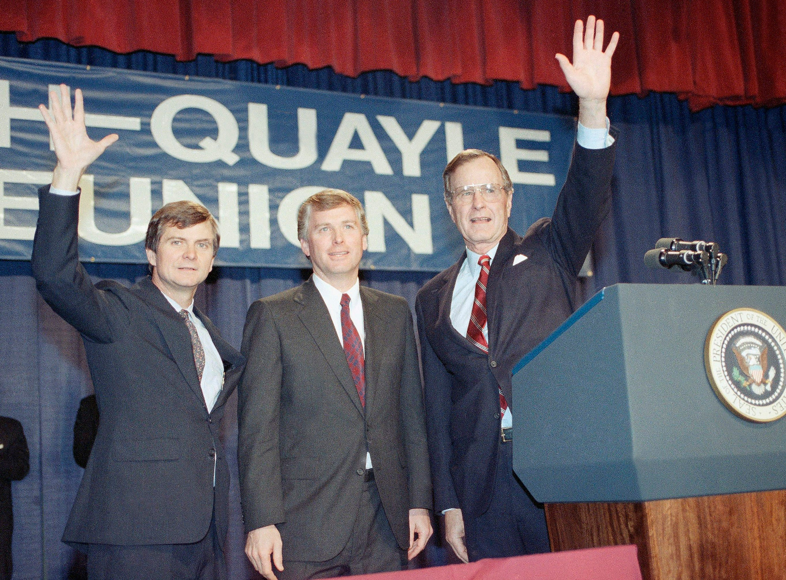 Pres. George H. W. Bush, right, Vice Pres. Dan Quayle, and political consultant Lee Atwater, left, wave to a crowd of campaign workers at a hotel to celebrate the first year of the Bush administration, Thursday, Jan. 18, 1990, Washington, D.C. Bush said All of America has triumphed in his first year in office and again prodded Congress to action his unfinished domestic agenda. (AP Photo/Charles Tasnadi)