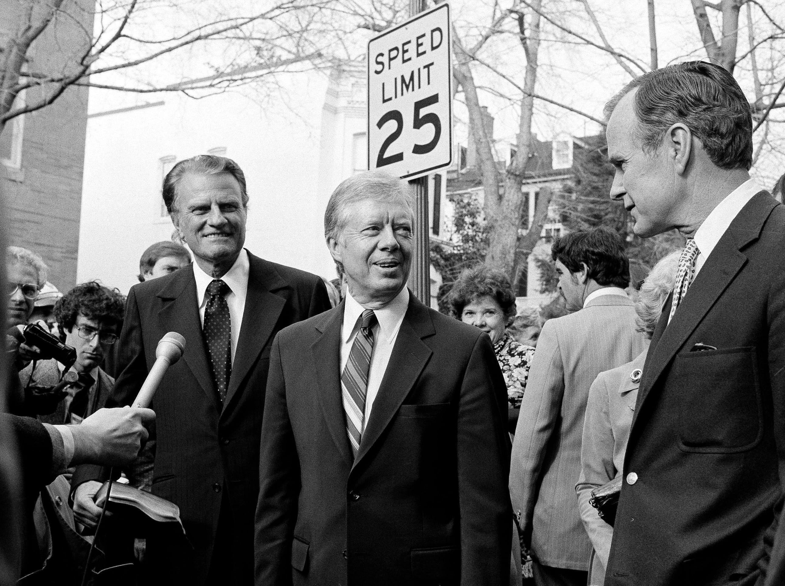 President Jimmy Carter answers a reporter's question outside the Georgetown Baptist Church in Washington, Dec. 7, 1980, where the Rev. Billy Graham held services.  Vice President-elect George Bush, right, is seen at right.  (AP Photo/Dennis Cook)