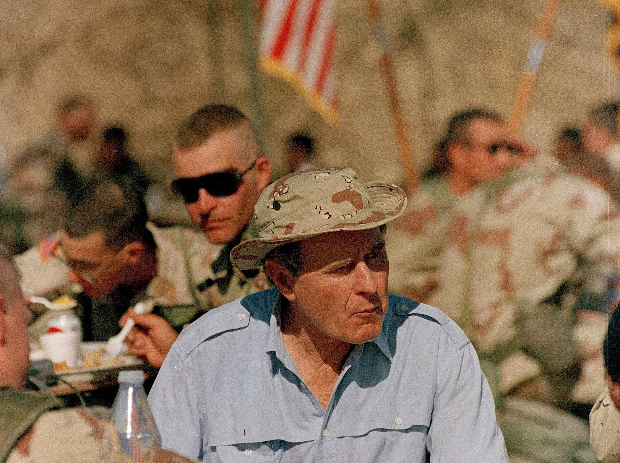 President George Bush shares a Thanksgiving dinner Thursday, Nov. 22, 1990, with U.S. troops at an army encampment in the Saudi desert.  (AP Photo/J. Scott Applewhite)
