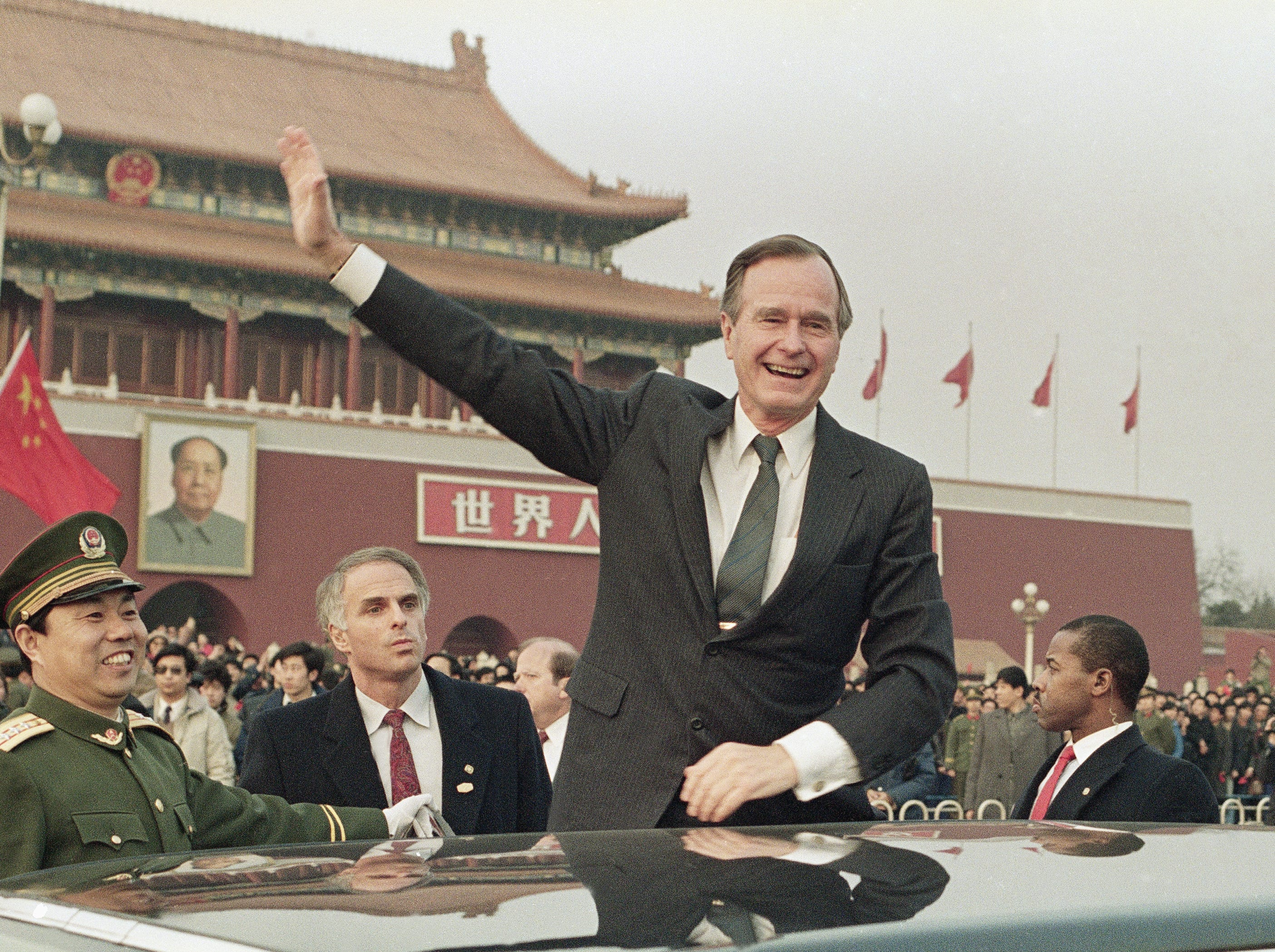 FILE - In this Feb. 25, 1989, file photo President George H.W. Bush stands on his car and waves to the crowds in Tiananman Square in Beijing. On the wall in the background is a huge portrait of Mao Zidong at the entrance to the Forbidden City. A president's first 100 days can be a tire-squealing roar from the starting line, a triumph of style over substance, a taste of what's to come or an ambitious plan of action that gets rudely interrupted by world events. (AP Photo/Doug Mills, File)