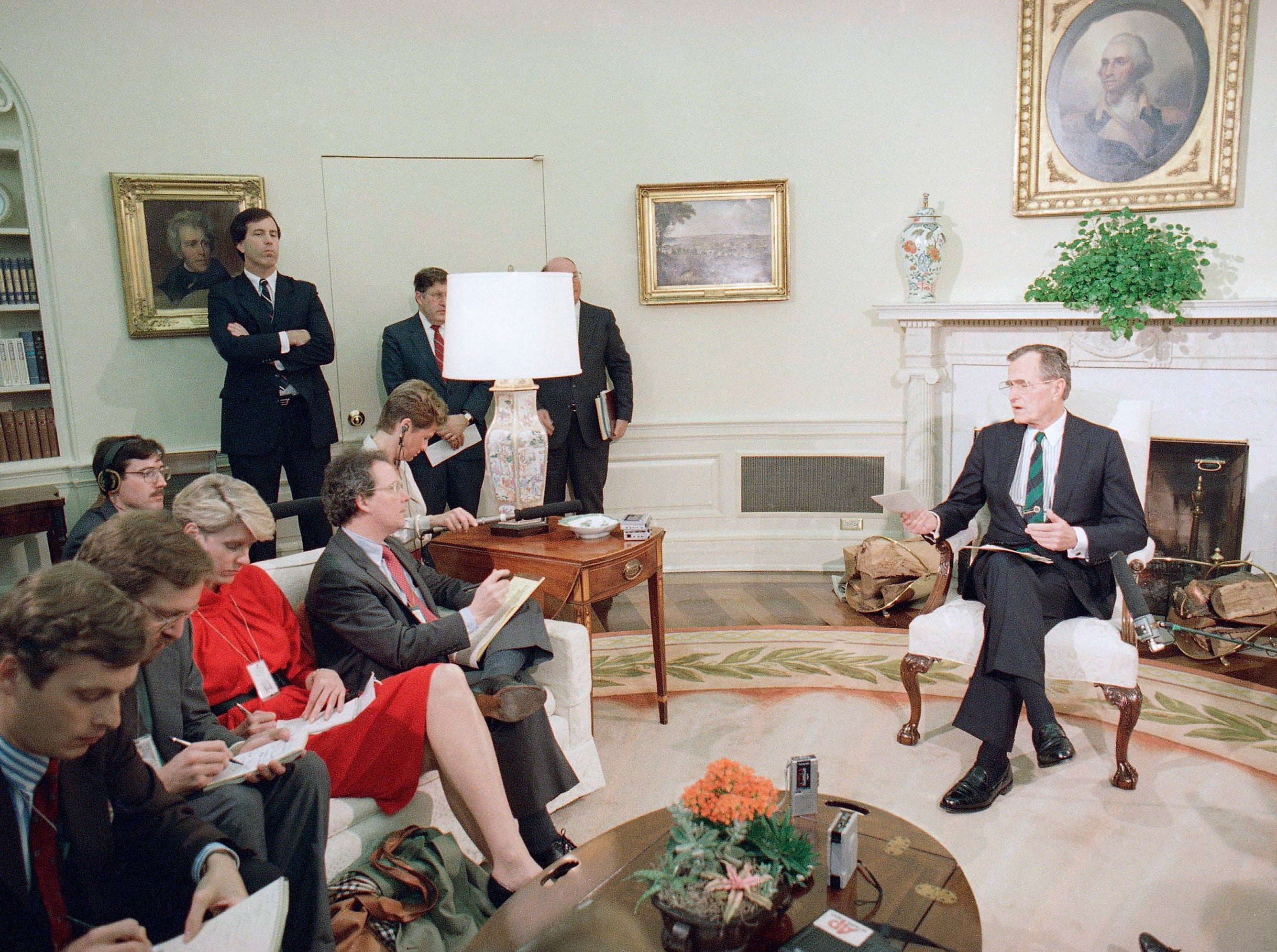 Pres. George H. W. Bush, right, meets with unidentified reporters in the Oval Office of the White House, Thursday, Feb. 17, 1989, Washington, D.C. Bush vowed to continue helping the Afghan rebels after the Soviet Red Army withdrawal from the war-ravaged Asian nation, but said he prefers a peaceful reconciliation. (AP Photo/Scott Applewhite)
