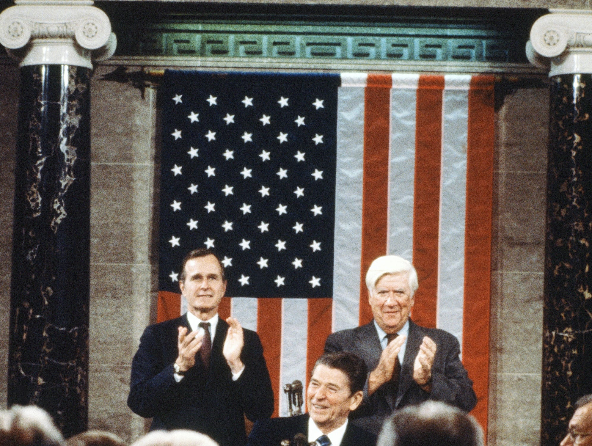 President Ronald Reagan addresses Congress on economic program with George H.W. Bush and Tip O'Neil on April 28, 1981. This was his first public appearance after being shot. (AP Photo)