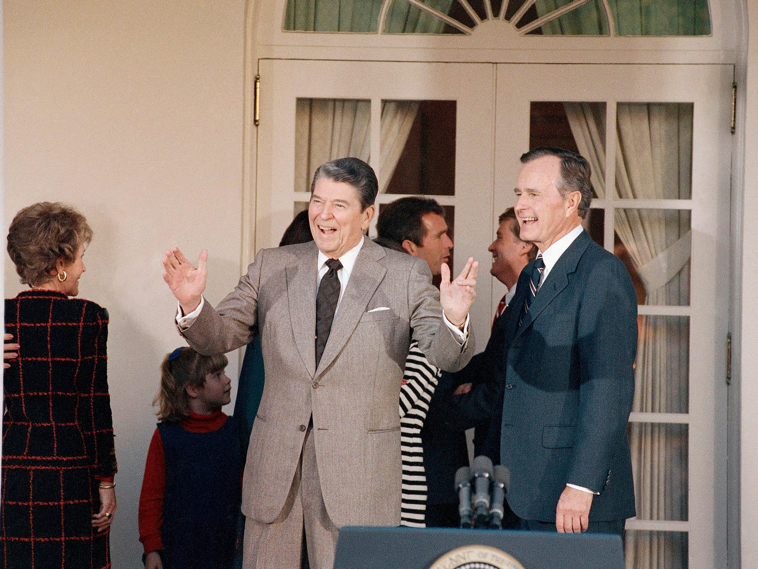 Pres. Ronald Reagan, left, responds to a reporter as President-elect George H. W. Bush, right, looks on following a Rose Garden ceremony at the White House, Wednesday, Nov. 9, 1988, Washington, D.C. (AP Photo/Charles Tasnadi)