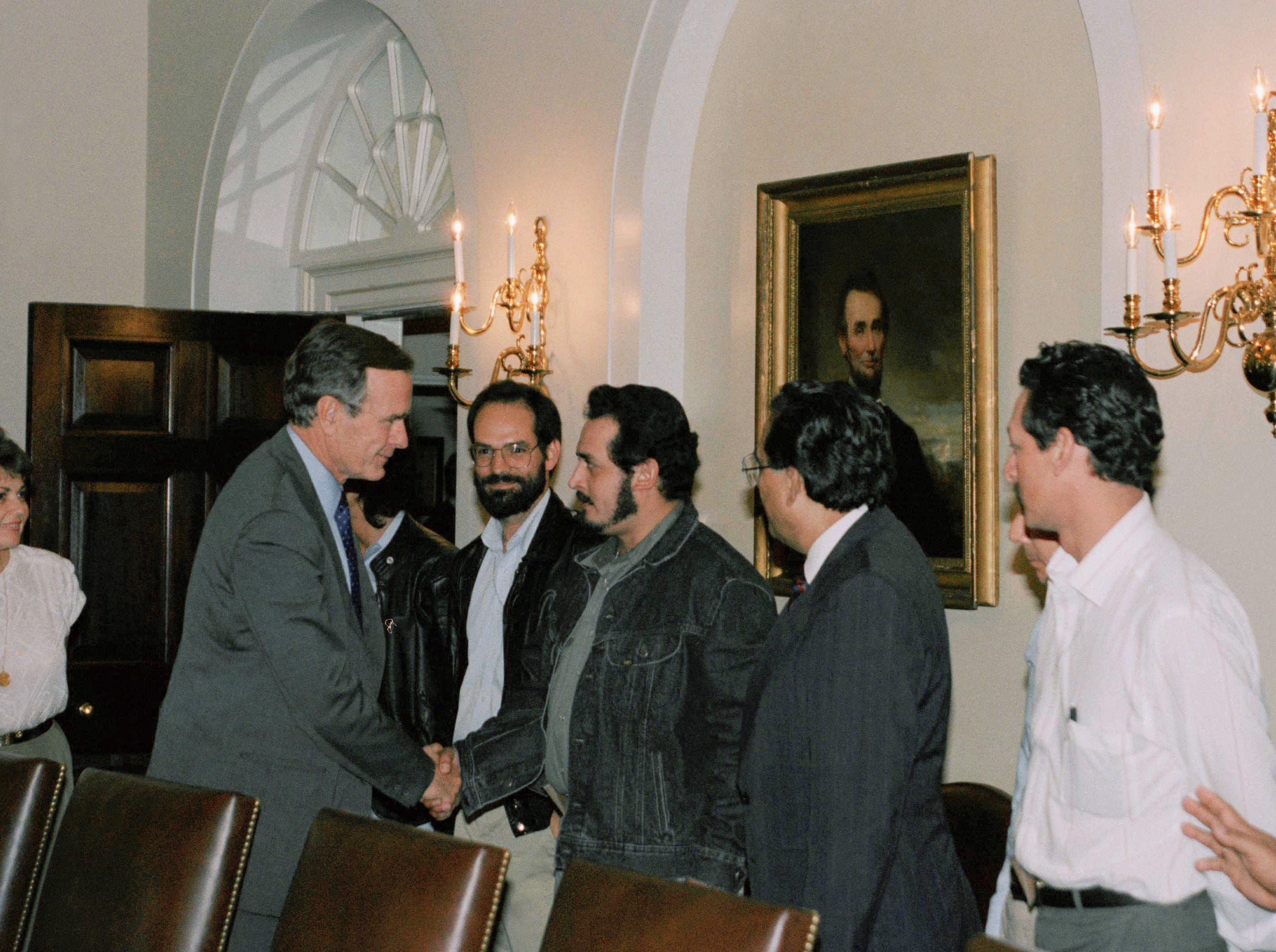 President George Bush meets with Contra leaders at the White House, Aug. 4, 1989 in Washington. From left with the president are Contra political adviser Xavier Arguello, Israel Galeano, the chief of staff of the Nicaraguan resistance's northern front, and Commanding General Enrique Bermudez. (AP Photo/Dennis Cook)