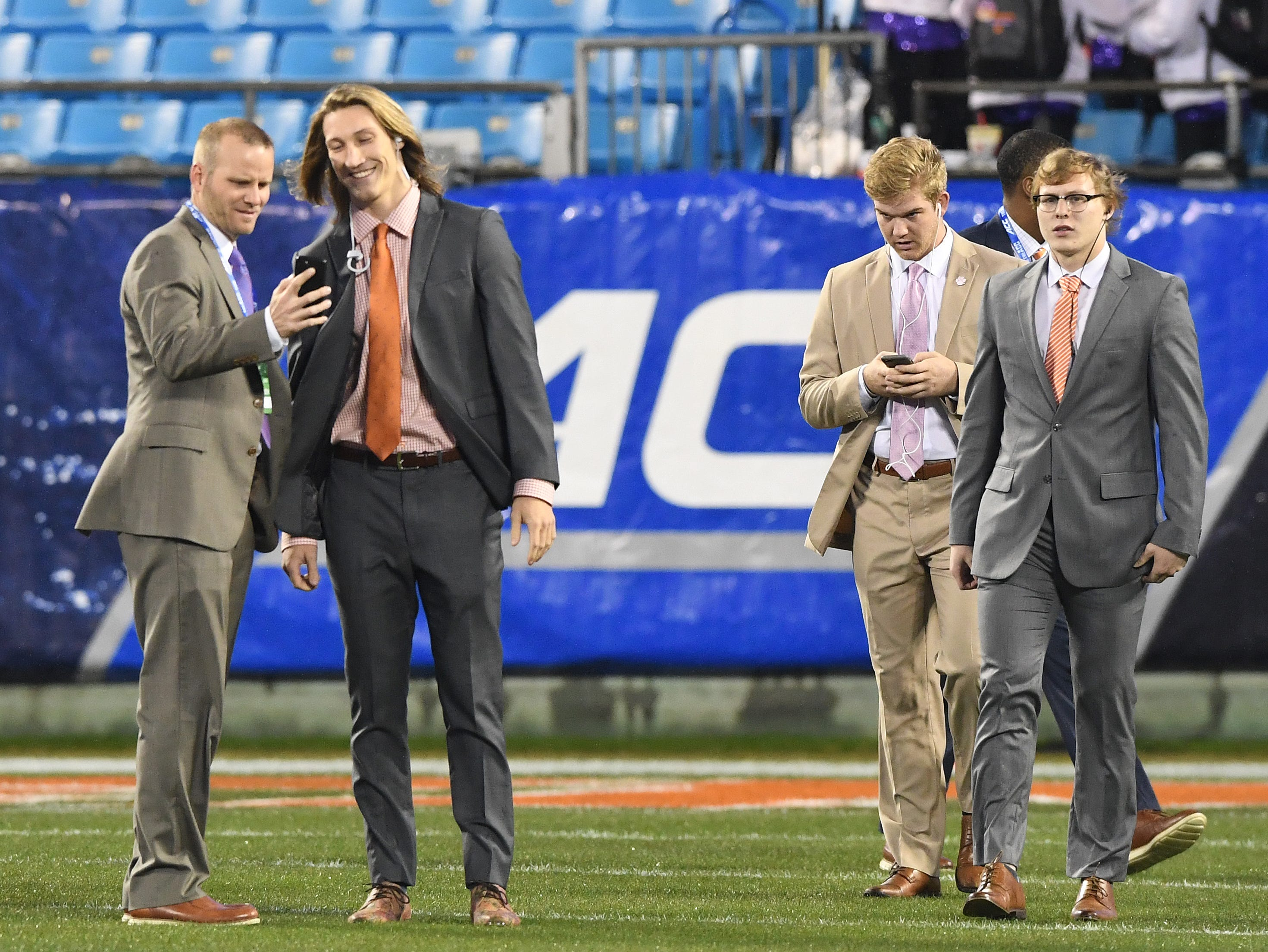Clemson quarterback Trevor Lawrence and quarterbacks coach Brandon Streeter on the field after arriving at Bank of America Stadium in Charlotte, N.C. for the Dr. Pepper ACC Championship Saturday, December 1, 2017.