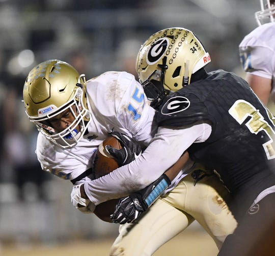 Greer's McZavion Holley (34) stops Daniel's Billy Bruce (15) in the class AAAA upstate championship Friday, November 30, 2018 at Greer's Dooley Field.