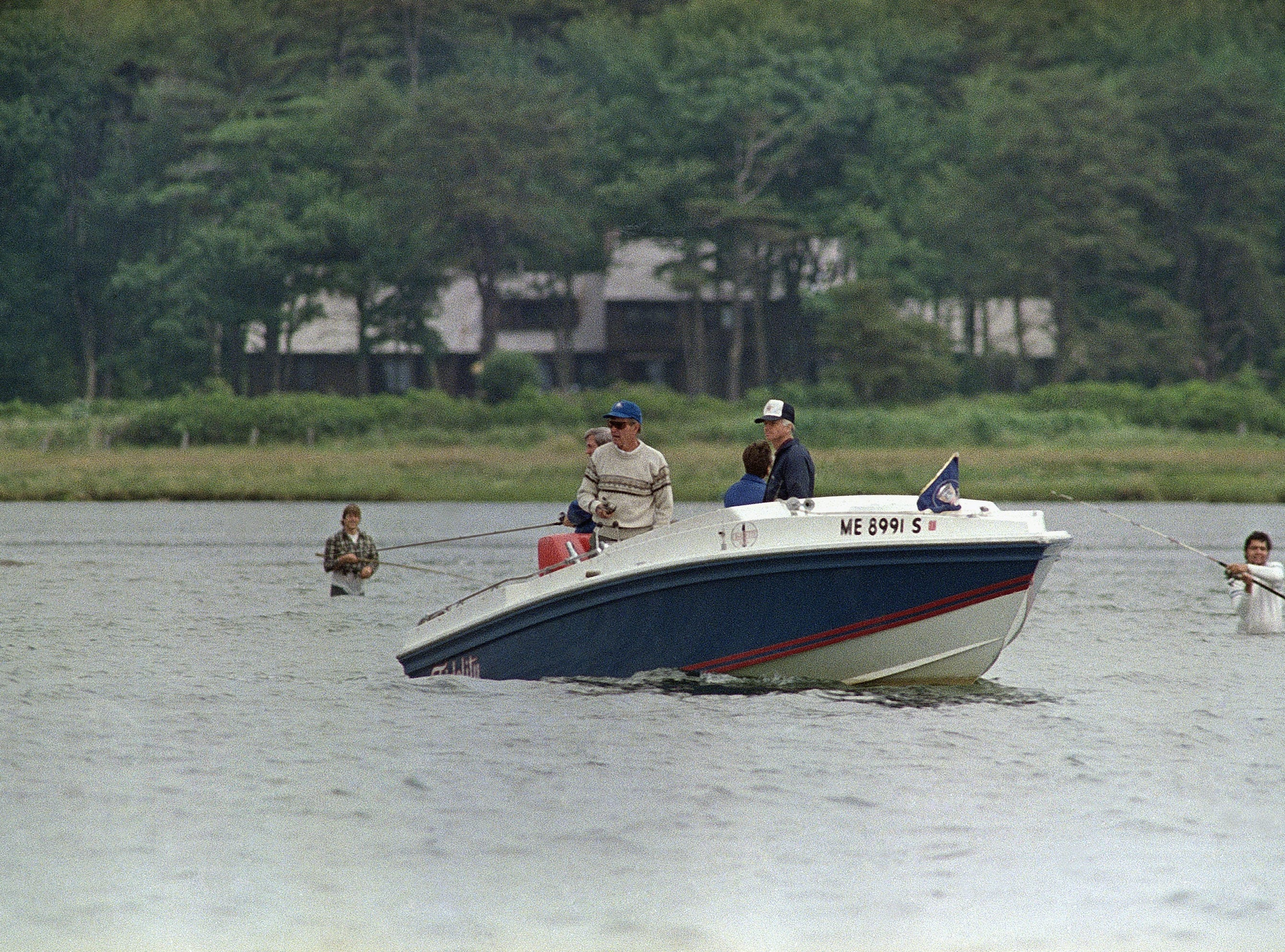 President George H. W. Bush in boaton left, fishes for striped bass at the mouth of the Mousam River in Kennebunk, Maine, Monday, July 3, 1989. Alongside his boat Fidelity, are fishermen in waders trying their luck, too. (AP Photo/Herb Swanson)