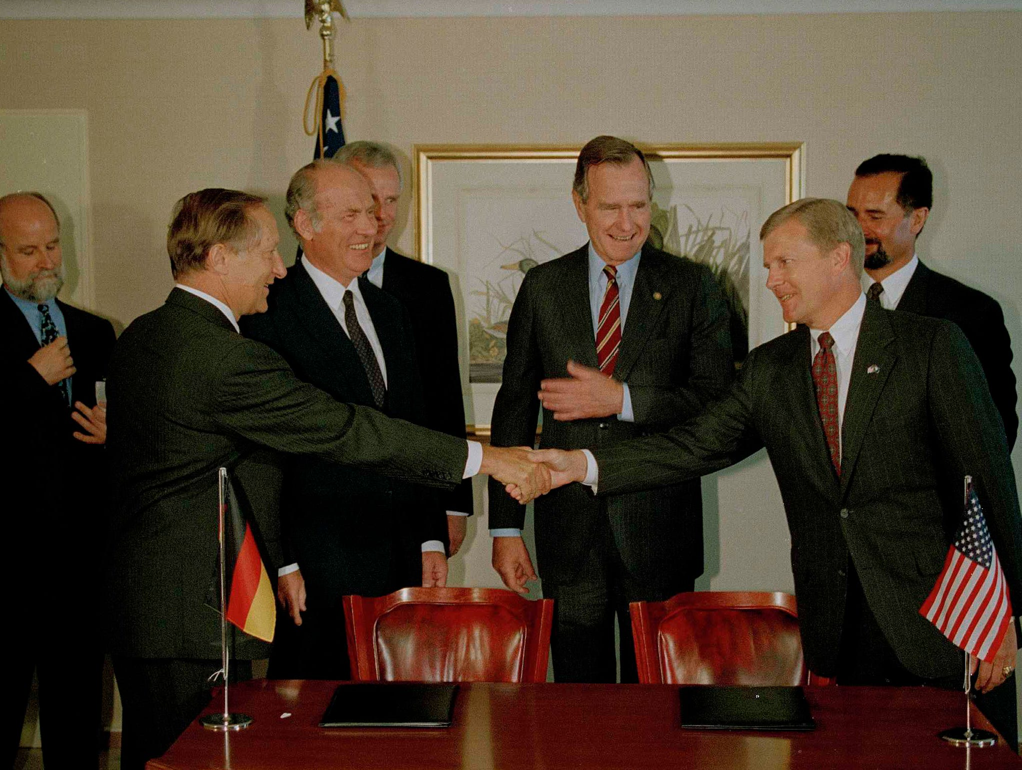 South Carolina Gov. Carroll Campbell, left, shakes hands with BMW chairman Eberhard von Kuenheim, right, as President George Bush looks on at center at Munich's Sheraton Hotel, July 6, 1992. The governor and von Kuenheim signed a treaty for BMW to build a factory for automobiles in Spartanburg, S.C. (AP Photo/Doug Mills)