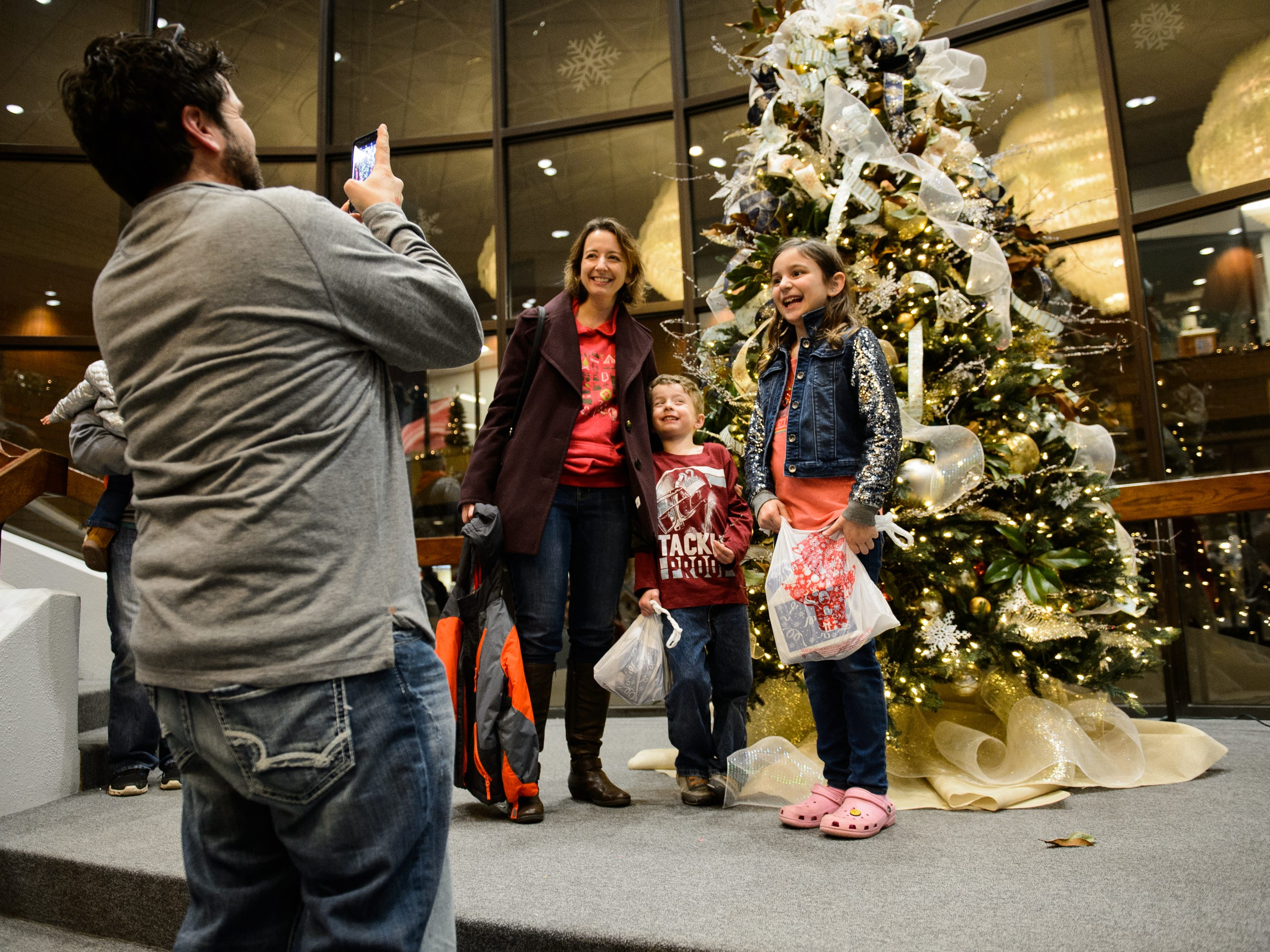 Kasey McClure takes a photo of his wife Susan, daughter Ellie and son Kasey Paul Jr. during Bob Jones University's annual Christmas Celebration on Friday, Nov. 30, 2018.