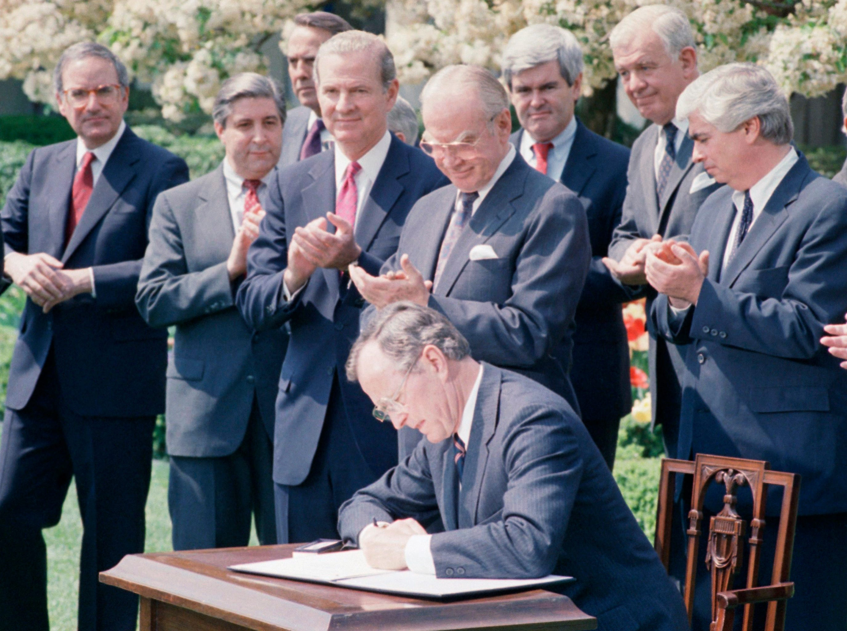 President Bush signs a Central American Bipartisan accord on Tuesday, April 18, 1989 in the White House Rose Garden in Washington. Looking on are from left: Rep. Mickey Edwards, R-Okla; Sen. Robert Dole, R-Kan; Secretary of State James Baker; House Speaker Jim Wright of Texas and Rep Whip Newt Gingrich of Ga. (AP Photo/Barry Thumma)
