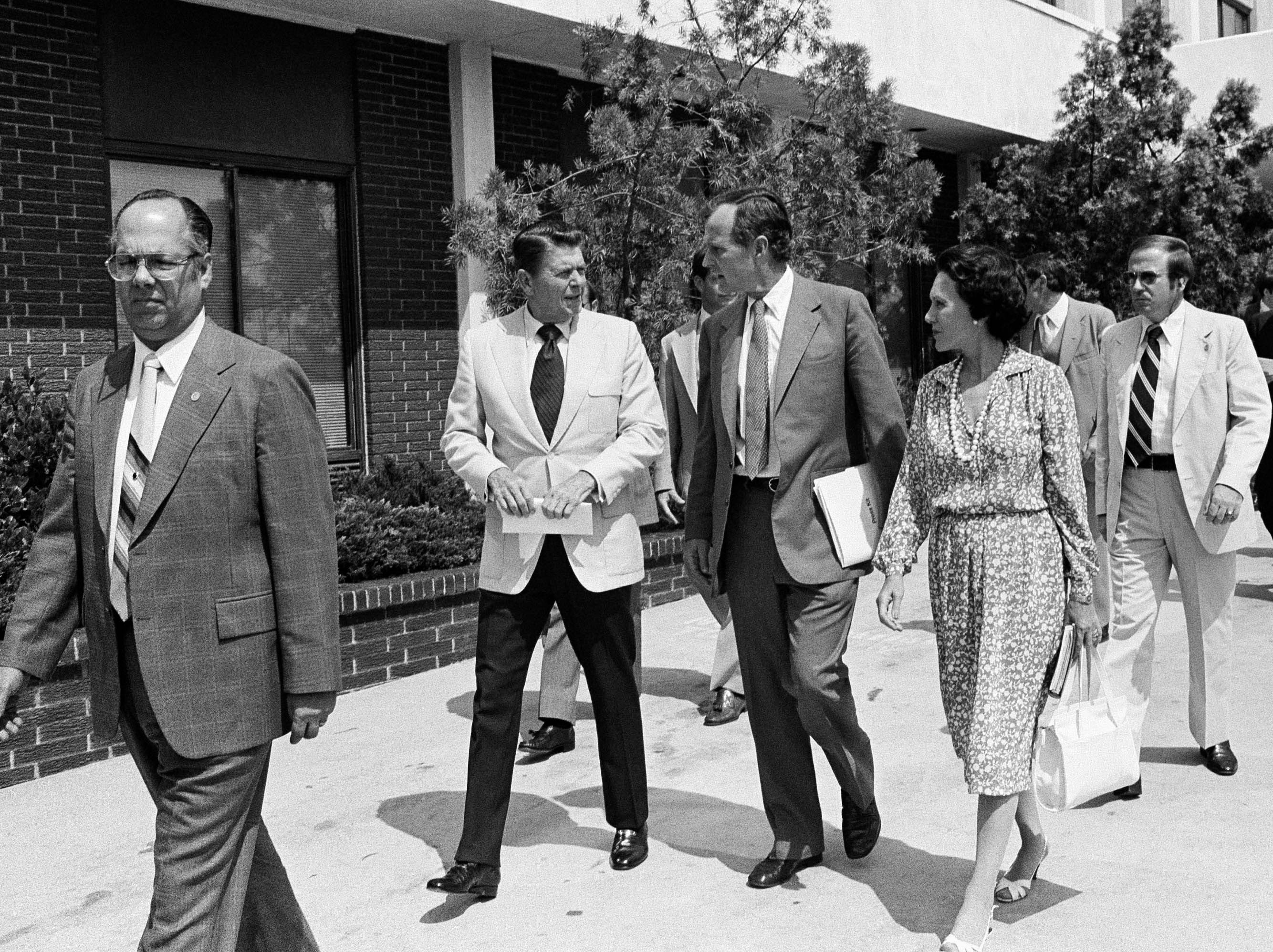 Republican presidential nominee Ronald Reagan, accompanied by vice-presidential nominee George H.W. Bush and Anne Armstrong, at right,  Reagan's newly appointed campaign co-chairperson, head for a news conference in Los Angeles on July 25, 1980. Reagan announced he and Bush are successfully merging their campaigns. Unidentified security people accompany the nominee. (AP Photo/Wally Fong)