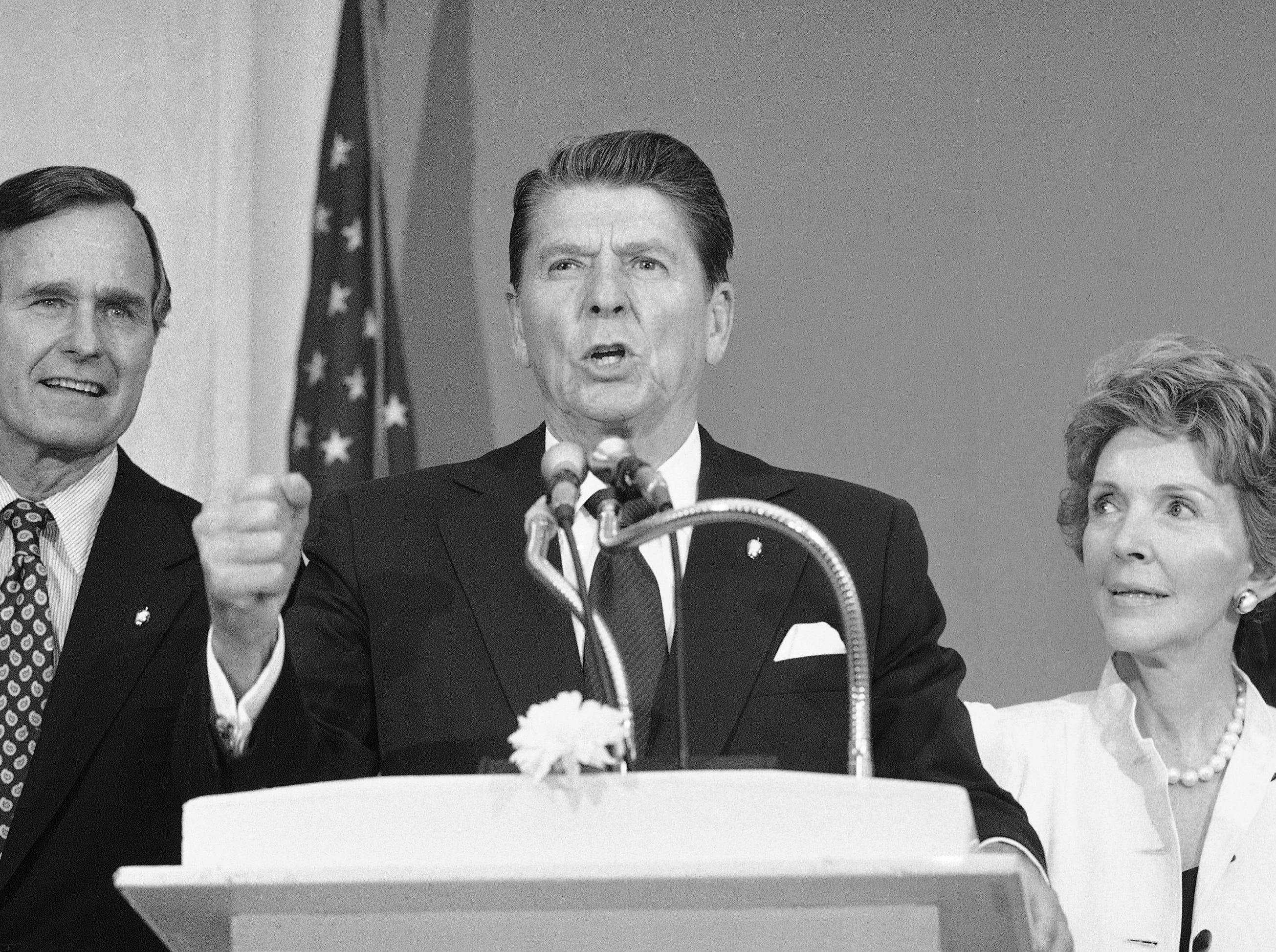Presidential hopeful Ronald Reagan, center, is flaked by his wife Nancy, and former opponent George Bush, as he delivers a speech at a reception in the New York Hotel Pierre on Monday, June 17, 1980 in New York. Reagan was in New York to meet with editorial boards and to continue his efforts to help his former Republican opponent pay off their campaign debts. (AP Photo/Lederhandler)