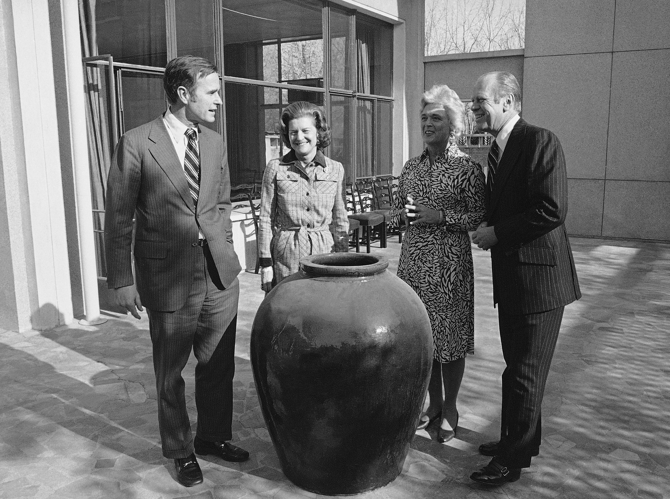 President Gerald Ford, right, and first lady Betty Ford, second from left, visit with George Bush, chief of the United States Liaison office, and his wife Barbara at the U.S. Liaison in Peking, China, Dec. 4, 1975.  (AP Photo)