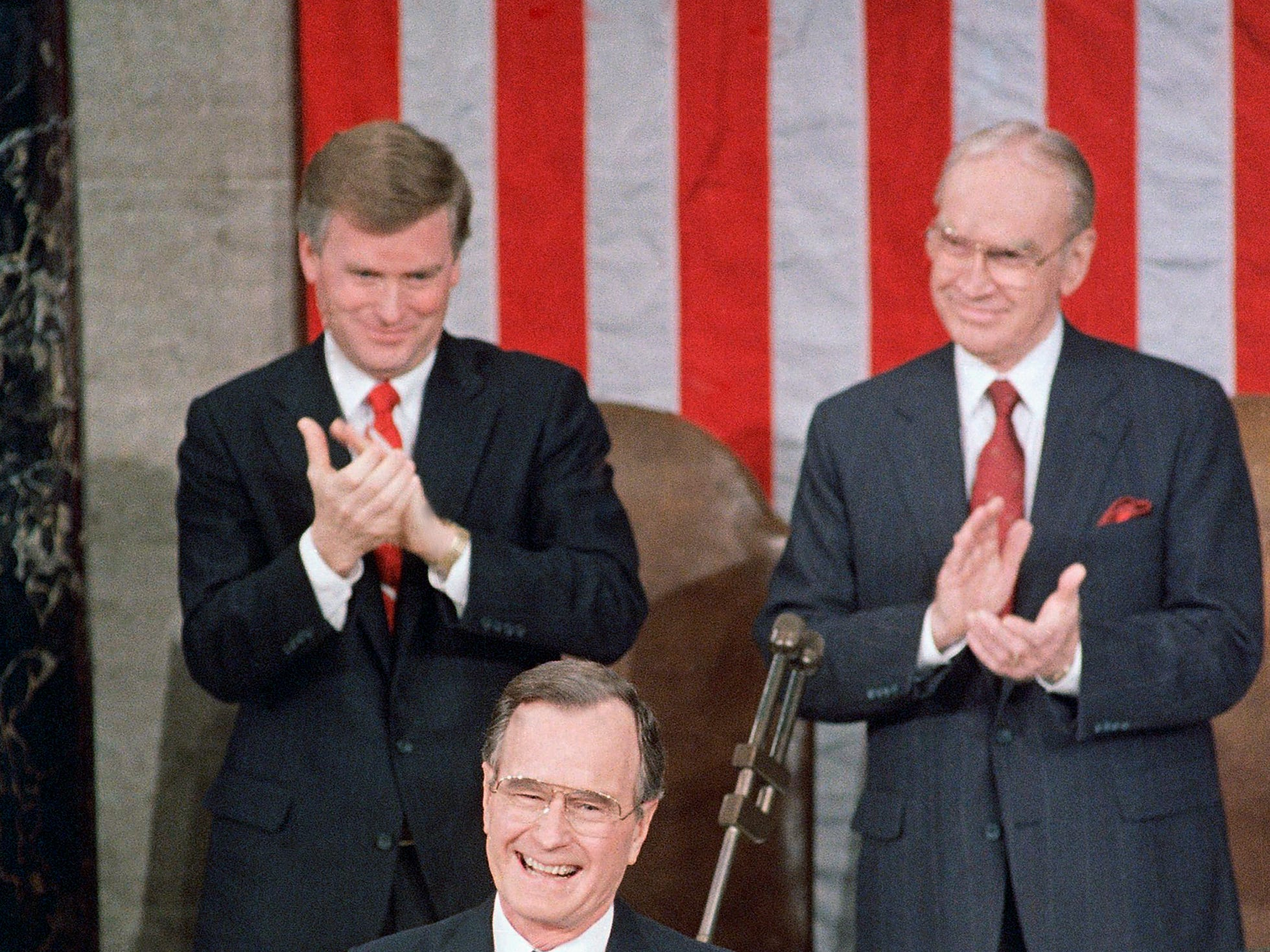 Pres. George H. W. Bush, front, acknowledges applause before addressing a Joint Session of Congress at the Capitol, Thursday, Feb. 9, 1989, Washington, D.C. Behind are Vice Pres. Dan Quayle and House Speaker Jim Wright. (AP Photo/Bob Daugherty)