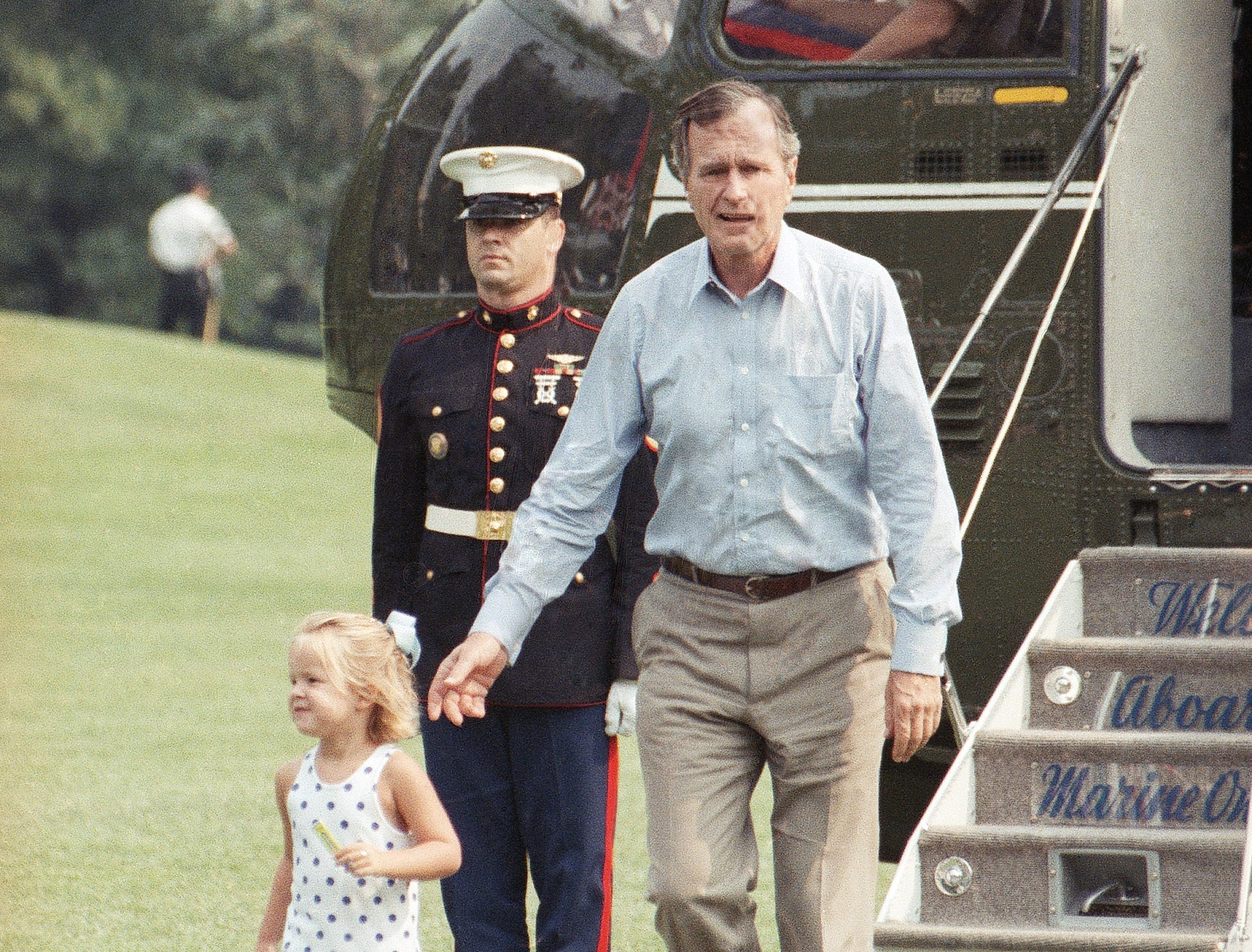 President George H. W. Bush follows his three-year-old granddaughter Marshall, down the steps of Marine One as they arrive July 23, 1989 at the White House in Washington after a weekend at Camp David. (AP Photo/Rick Bowmer)