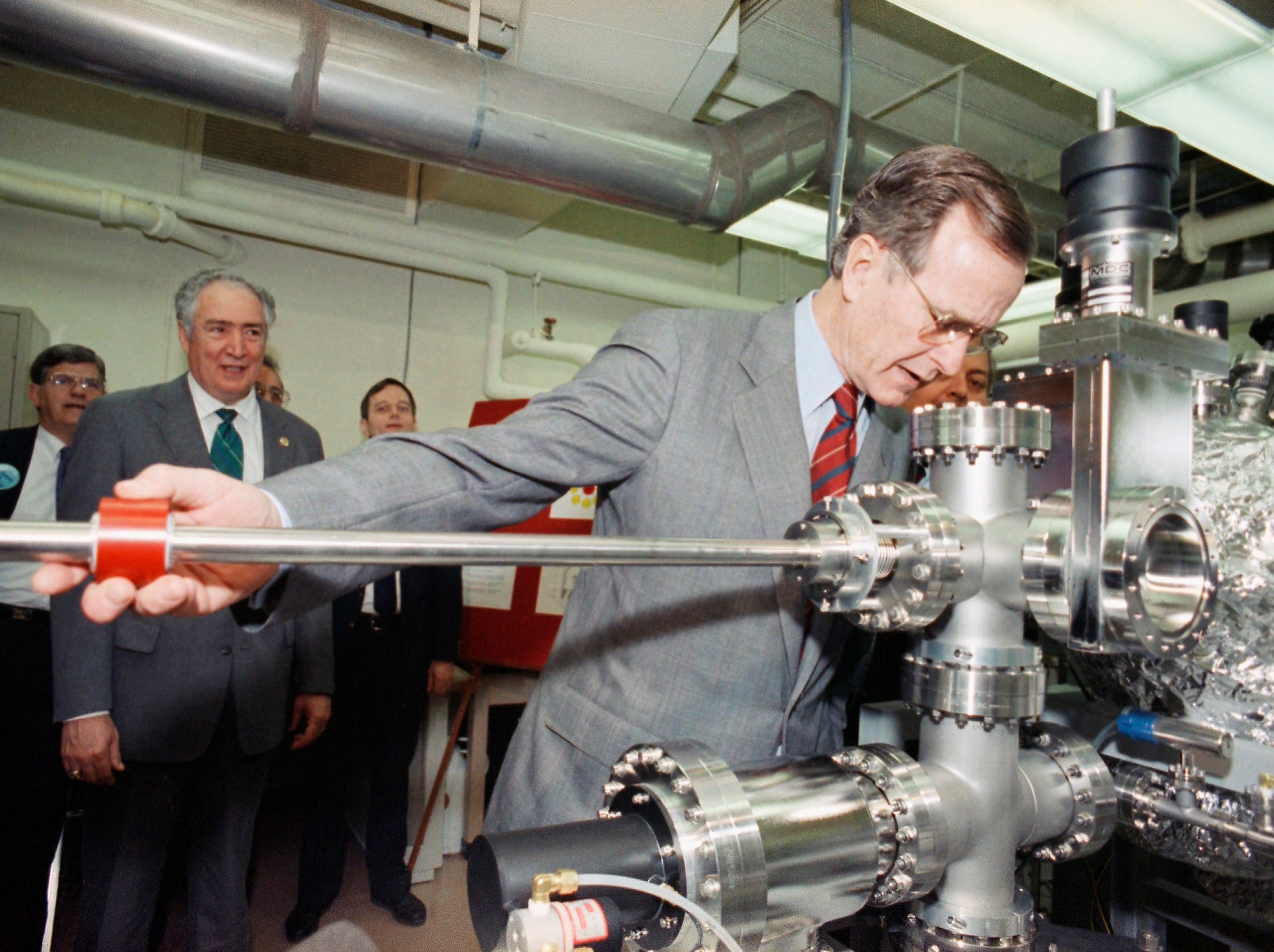 President George H.W. Bush looks through a ultraviolet photo emission spectrometer during a tour of a physics lab at North Carolina State University in Raleigh, N.C., on Friday, Feb. 2, 1990. (AP Photo/Dennis Cook)