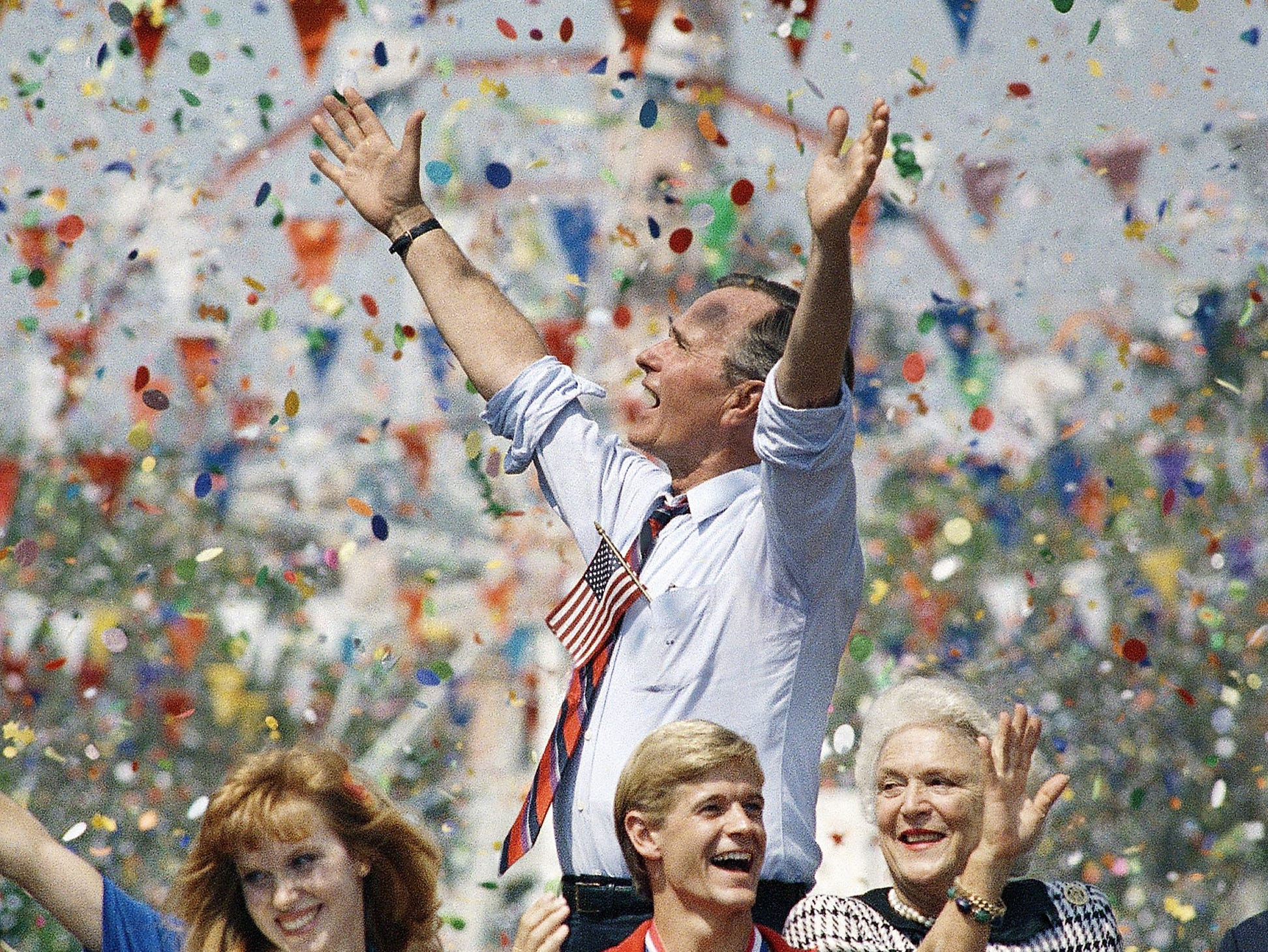 Vice President George H.W. Bush acknowledges the cheers from the crowd during a parade at  Disneyland in Anaheim, Calif. early in September 1988.  With him at right is his wife Barbara Bush and bottom center, UCLA gymnast and member of the Olympic team, Peter Vidmar.   Woman at left is unidentified. (AP Photo/J. Scott Applewhite)