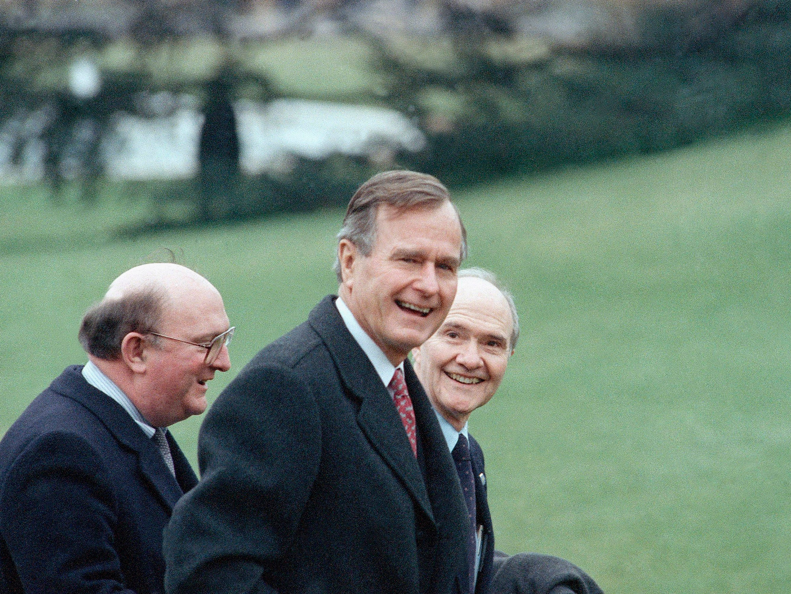 Pres. George H. W. Bush, center, arrives back at the White House in a light snow with National Security Adviser Brent Scowcroft, right, and Press Secretary Marlin Fitzwater after a speech in Manchester, N.H., Monday, Feb. 13, 1989, Washington, D.C. (AP Photo/Charles Tasnadi)