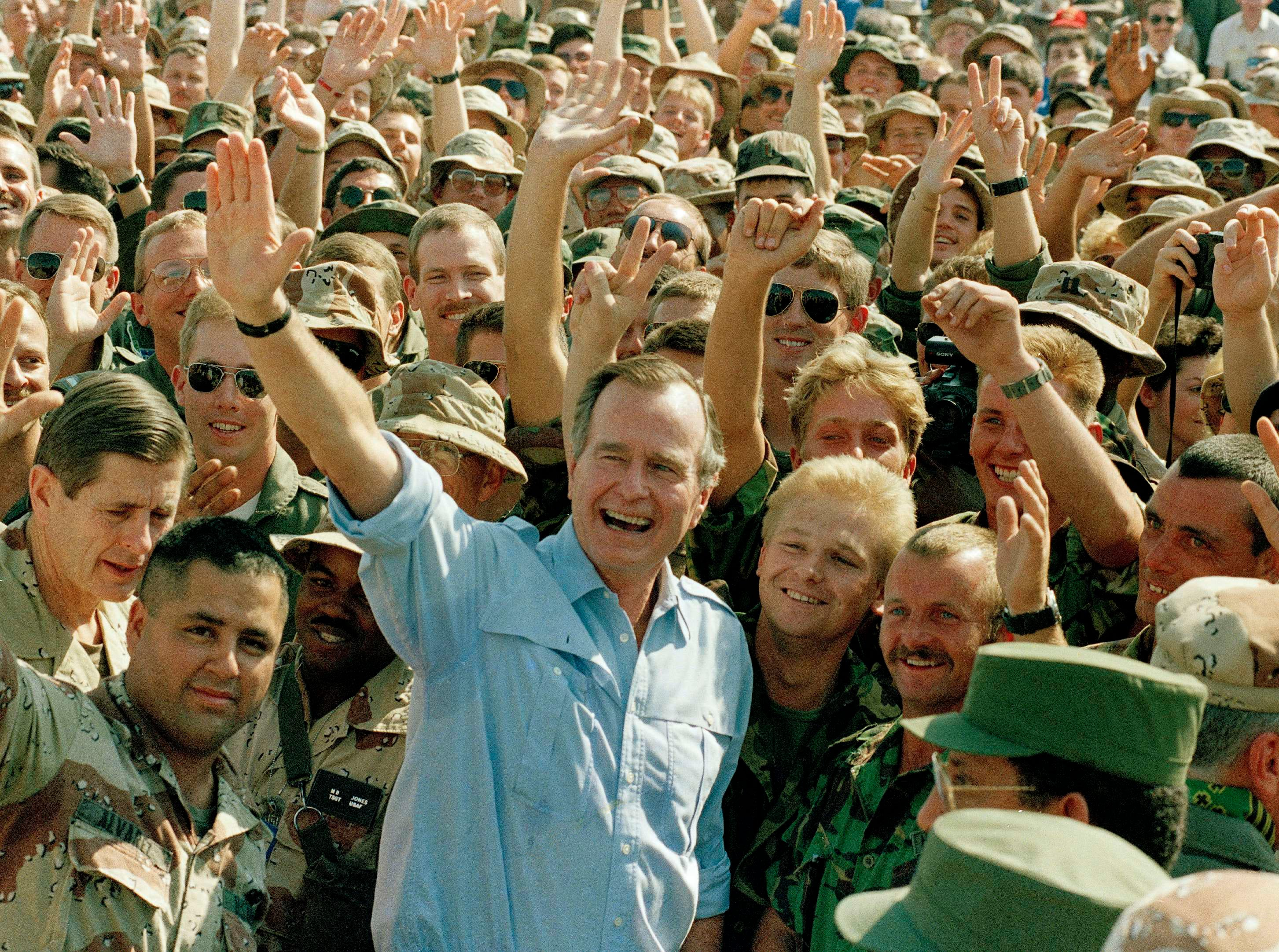 President George Bush poses with soldiers during a stop at an air base in Dhahran, Saudi Arabia, Nov. 22, 1990. (AP Photo/J. Scott Applewhite)