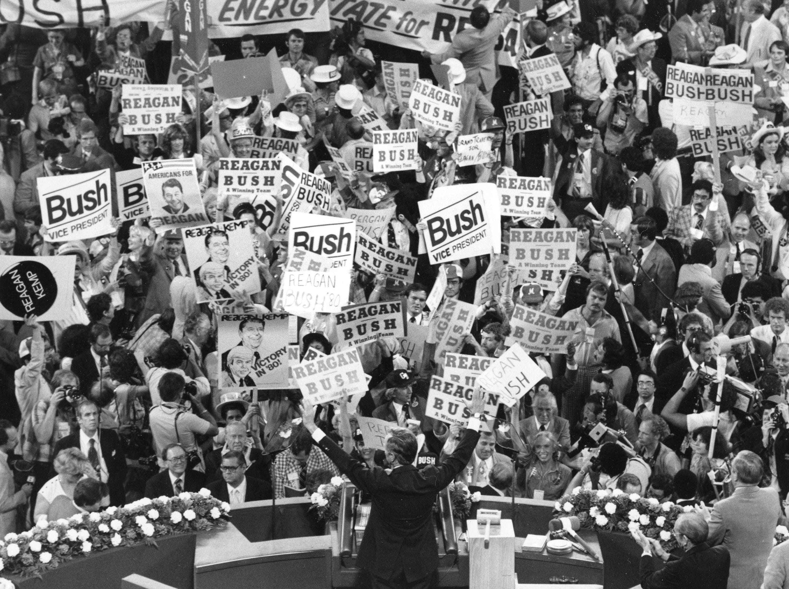 George Bush, foreground, raises his arms as a floor demonstration erupts before speaking to the Republican Convention delegates in Detroit, Mich., Wednesday evening, July 16, 1980.  Republican presidential candidate Ronald Reagan later announced Bush as his running mate.  (AP Photo)