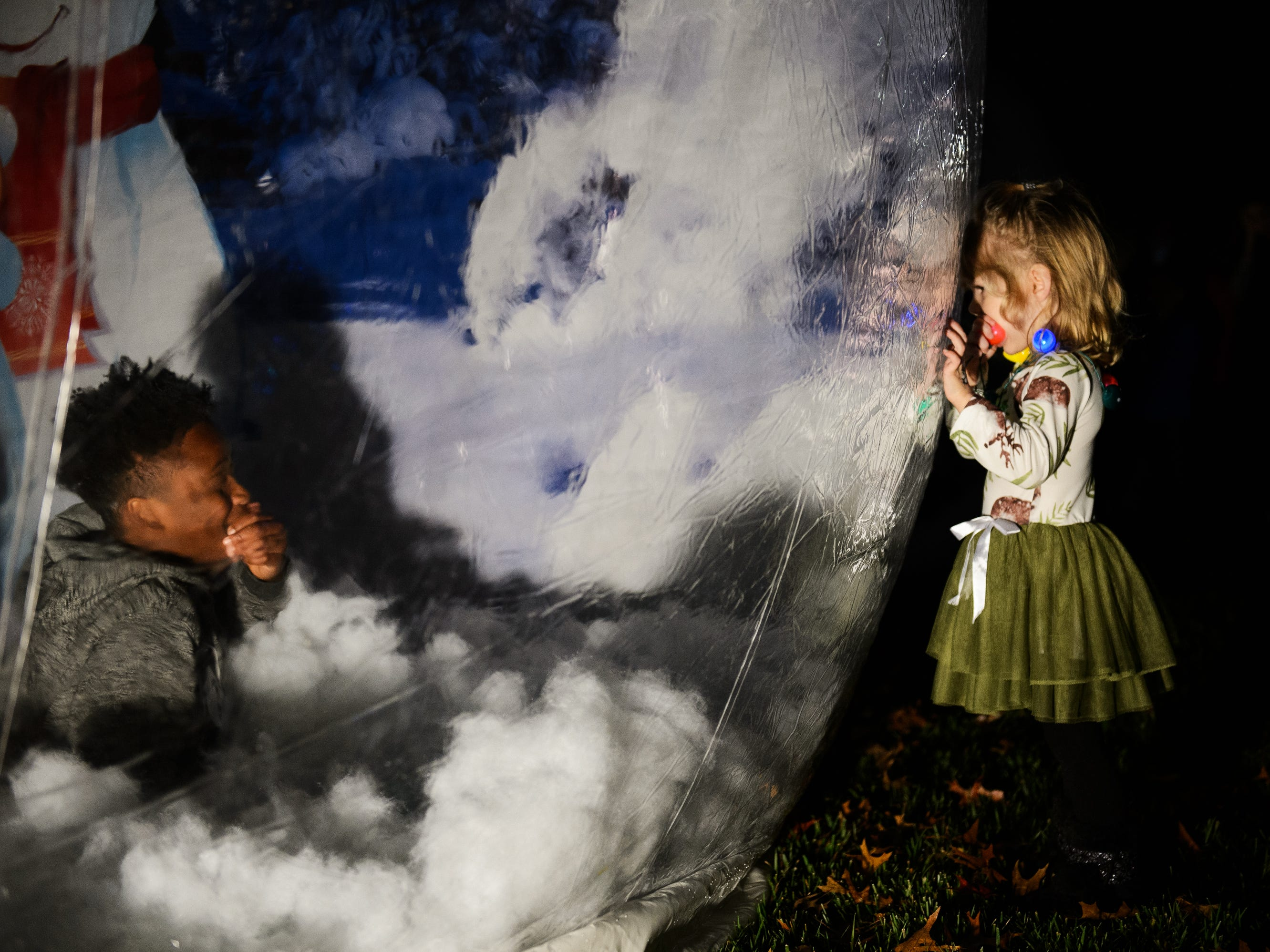 Lilly Byars, 3, peeks into a life-sized snow globe during Bob Jones University's annual Christmas Celebration on Friday, Nov. 30, 2018.