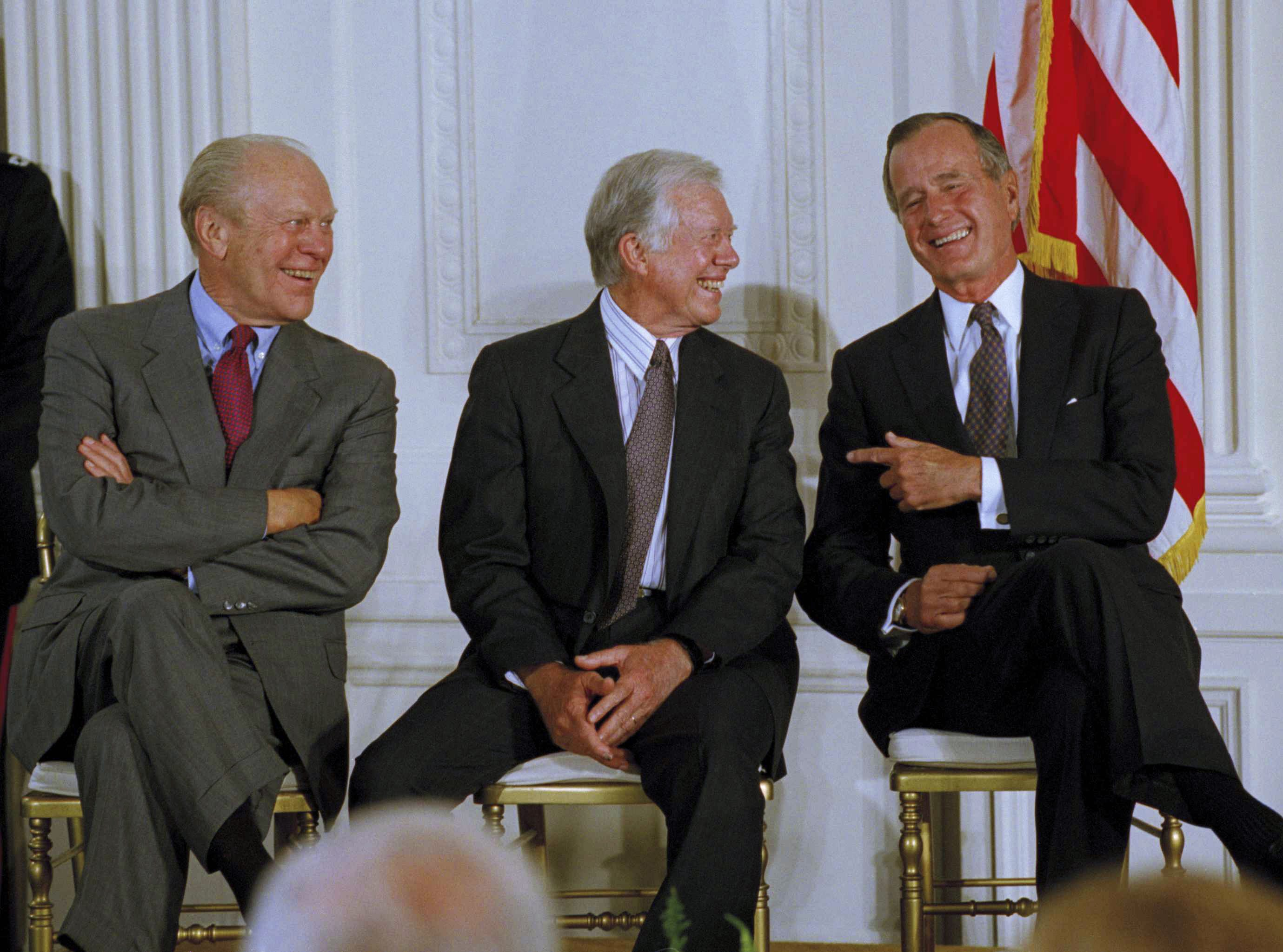 Former President George H.W. Bush, right, and former President  Jimmy Carter, center, share a laugh as former President Ford looks on at the White House in Washington Tuesday, Sept. 14, 1993.  The three former presidents joined President  Bill Clinton at a side deal signing of the three-nation North American Free Trade Agreement. (AP Photo/Ron Edmonds)