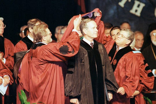 President George Bush receives an honorary Doctor of Laws degree during commencement exercises at the University of South Carolina, May 12, 1990 in Columbia, S.C.  At left is chairman of the board of trustees Michael J. Mungo and right Thomas L. Stepp, secretary to the board.  (AP Photo/Lou Krasky)