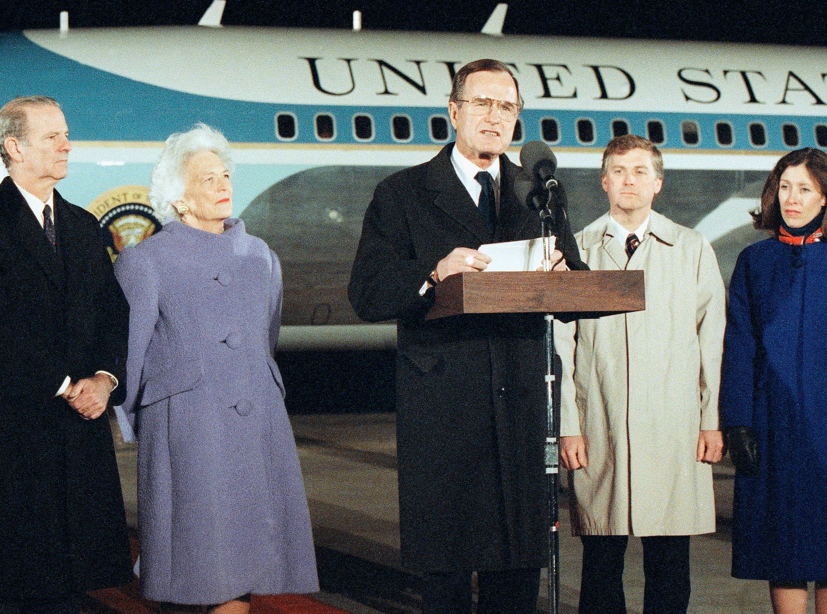 President George H. W. Bush, center, talks to reporters at the base of Air Force One, as he returns to the U.S. following a three nation, Far East visit, Monday, Feb. 28, 1989, Andrews AFB, Maryland. Bush pronounced the five-day Asian voyage a productive and rewarding journey and moved to take personal command of the struggle to win confirmation for John Tower as Defense Secretary. Flanking the president are First Lady Barbara Bush, left, and Vice President Dan Quayle and Marilyn Quayle, at right. The man on the left is unidentified. (AP Photo/Doug Mills)