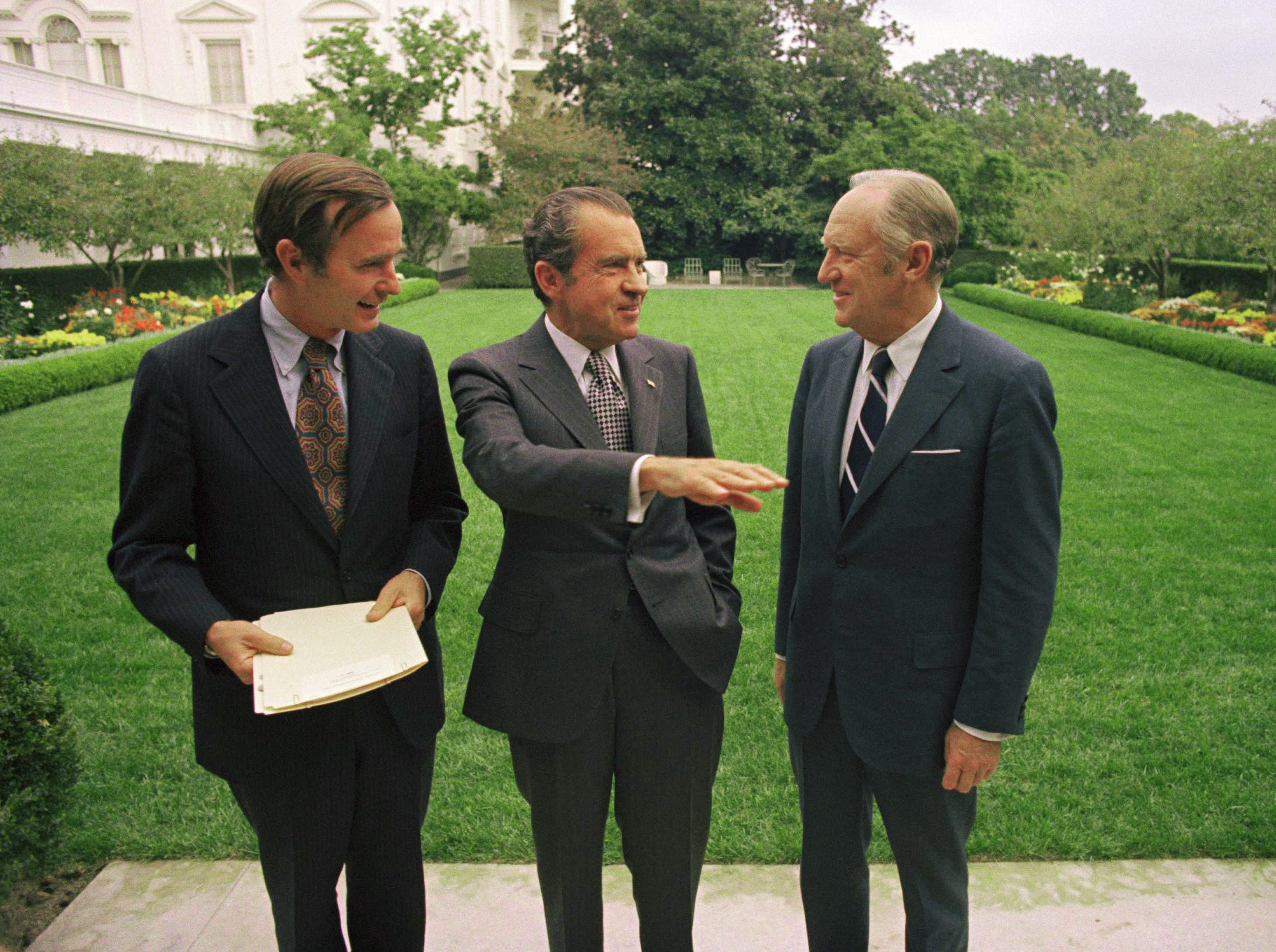 President Richard Nixon with Wm. Rogers, Sect. of State, right, and Geo Bush, U.N. Ambassador, left, in the Rose Garden at the White House in Washington on Oct. 22, 1971. (AP Photo/Henry Burroughs)