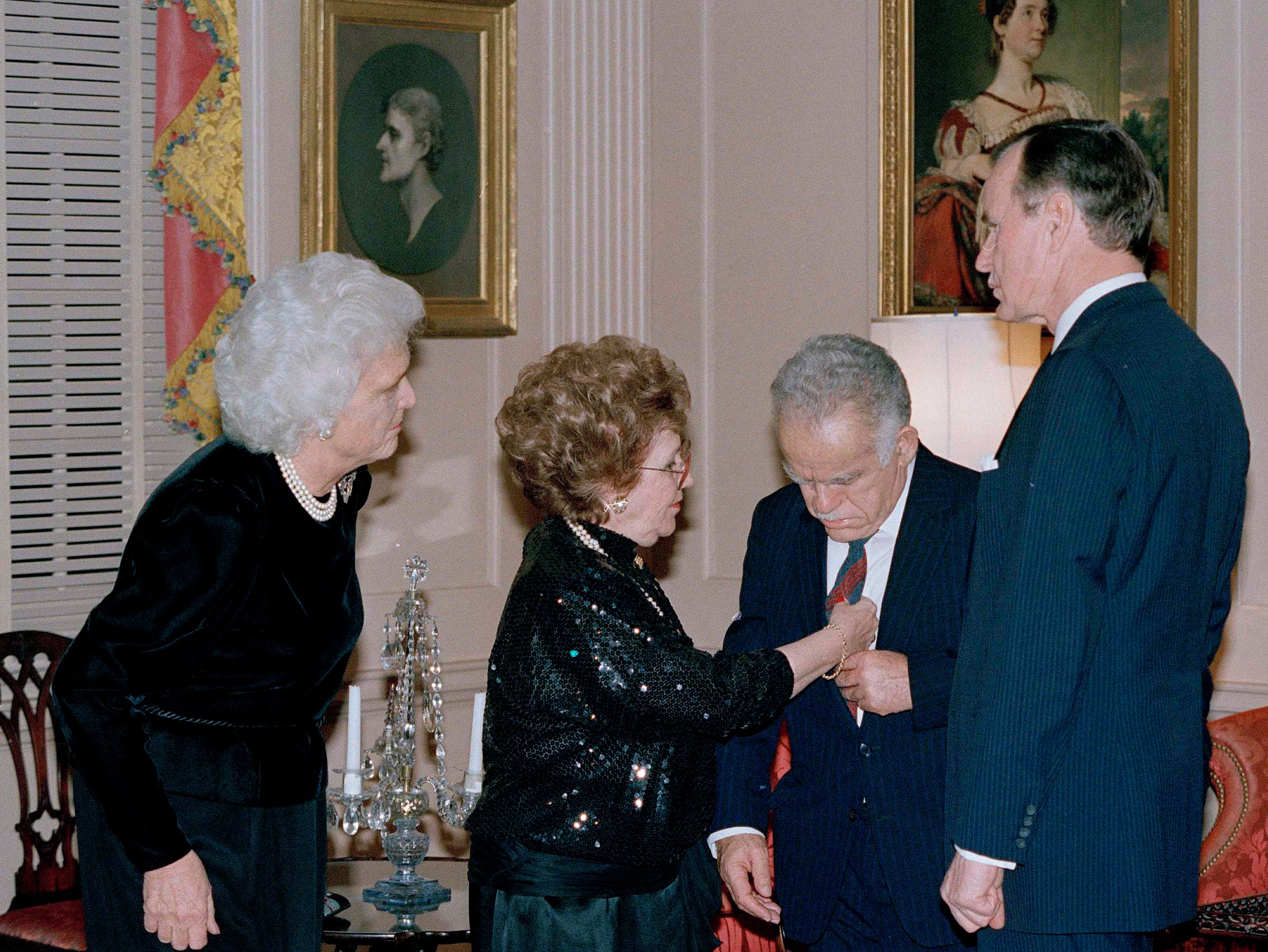 Israeli Prime Minister Yitzhak Shamir has his tie adjusted by his wife Shulamit before a dinner in their honor at the State Department in Washington, D.C., Feb. 19, 1987. At right is Vice President George Bush and at left is his wife Barbara. (AP Photo/Ira Schwarz)
