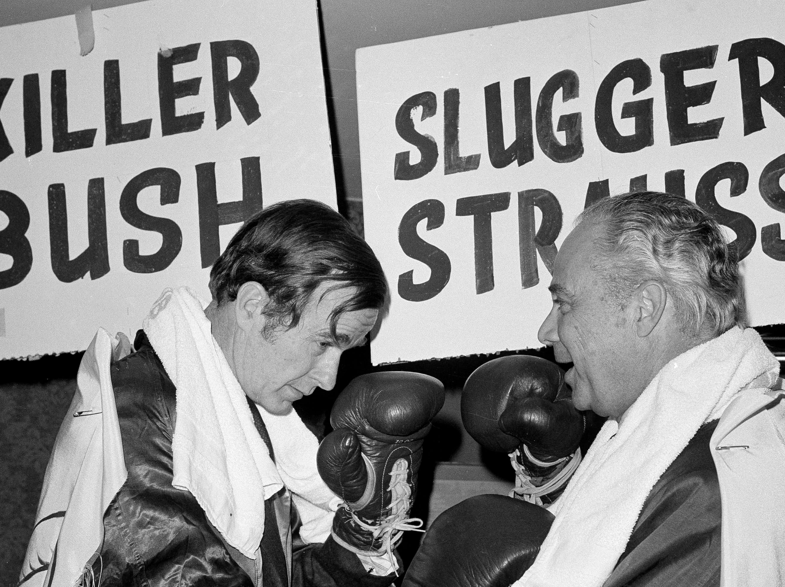 "Republican National Committee chairman George Bush, left, sizes up his opponent, Democratic National Committee chairman Robert S. Strauss, during the Circus Saints and Sinners Club luncheon in Washington, March 7, 1974. ""Killer"" Bush and ""Slugger"" Strauss donned the gloves for what was billed as the ""Battle of the Century."" (AP Photo/Henry Burroughs)"