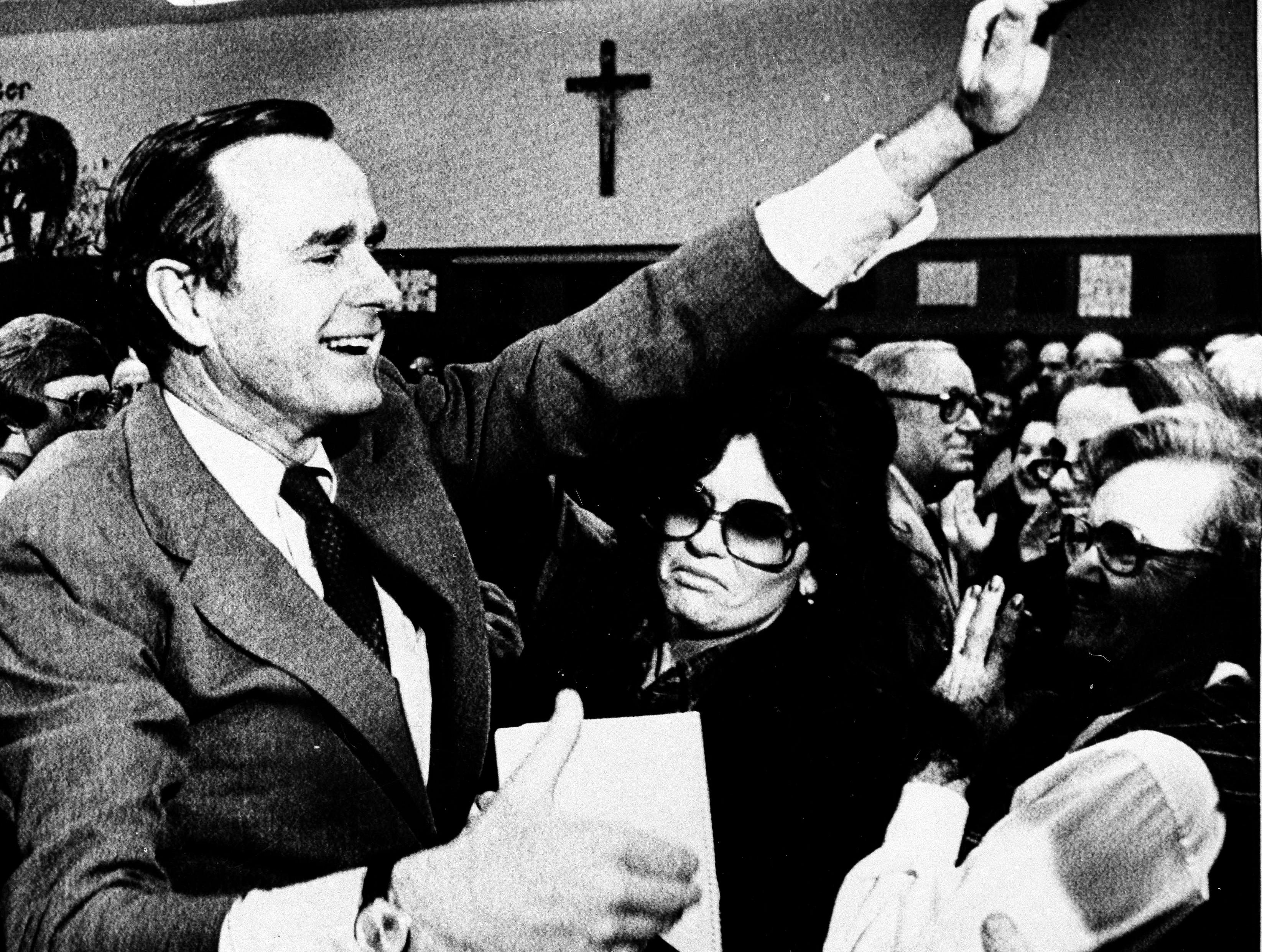 George Bush waves to acknowledge the applause of Iowa voters in the St. Augustin's precinct of Des Moines after he won a majority of votes there, Jan. 21, 1980. Bush toured several precincts in his bid for the Republican presidential nomination. (AP Photo/Jim Mone)
