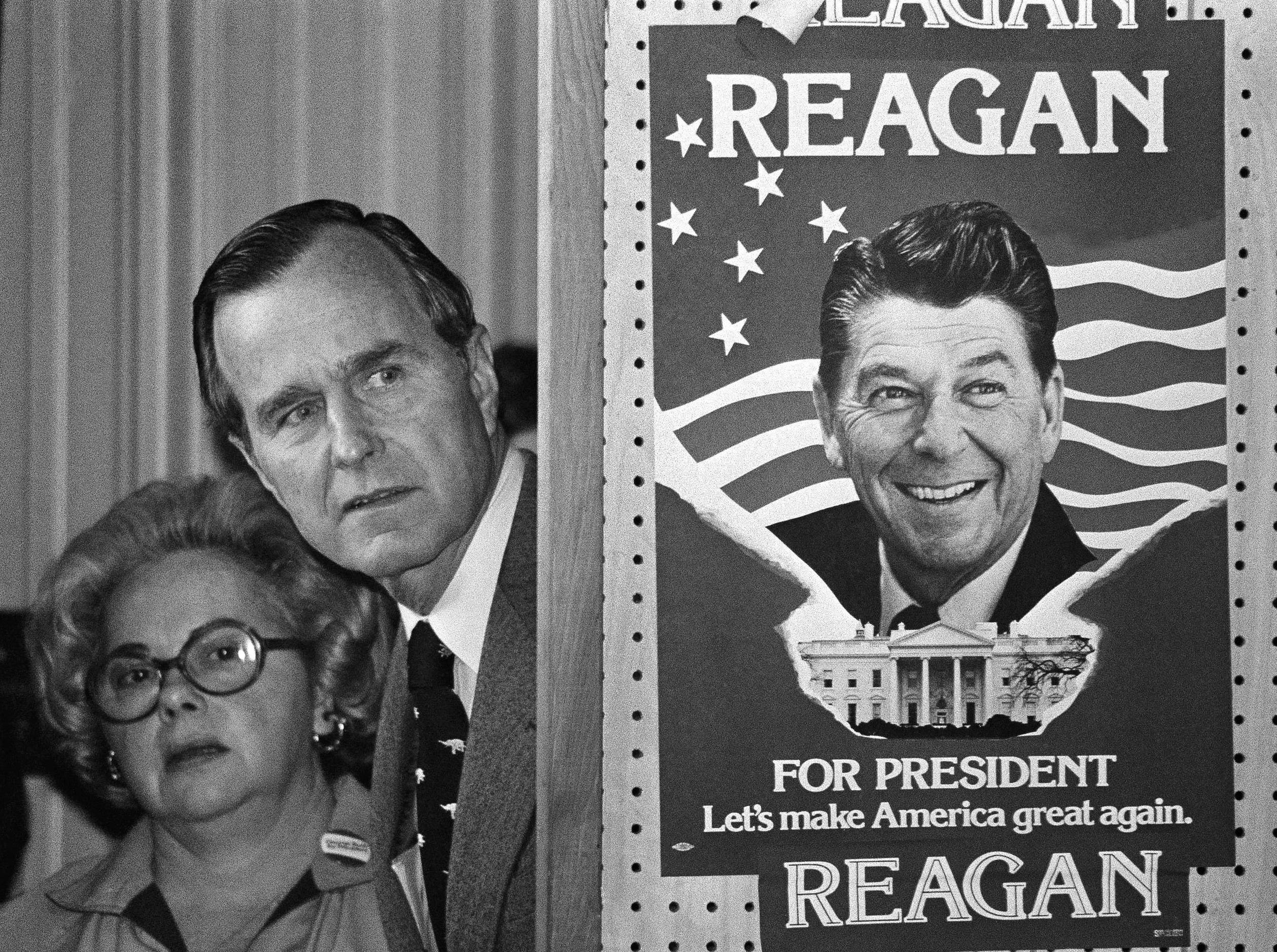 FILE - In this March 4, 1980 file photo, George H.W. Bush and an unidentified woman peek around a partition with a poster of Ronald Reagan, one of his opponents for the Republican party presidential nomination, before he speaks in Columbia, S.C. Bush has died at age 94. Family spokesman Jim McGrath says Bush died shortly after 10 p.m. Friday, Nov. 30, 2018, about eight months after the death of his wife, Barbara Bush. (AP Photo, File)