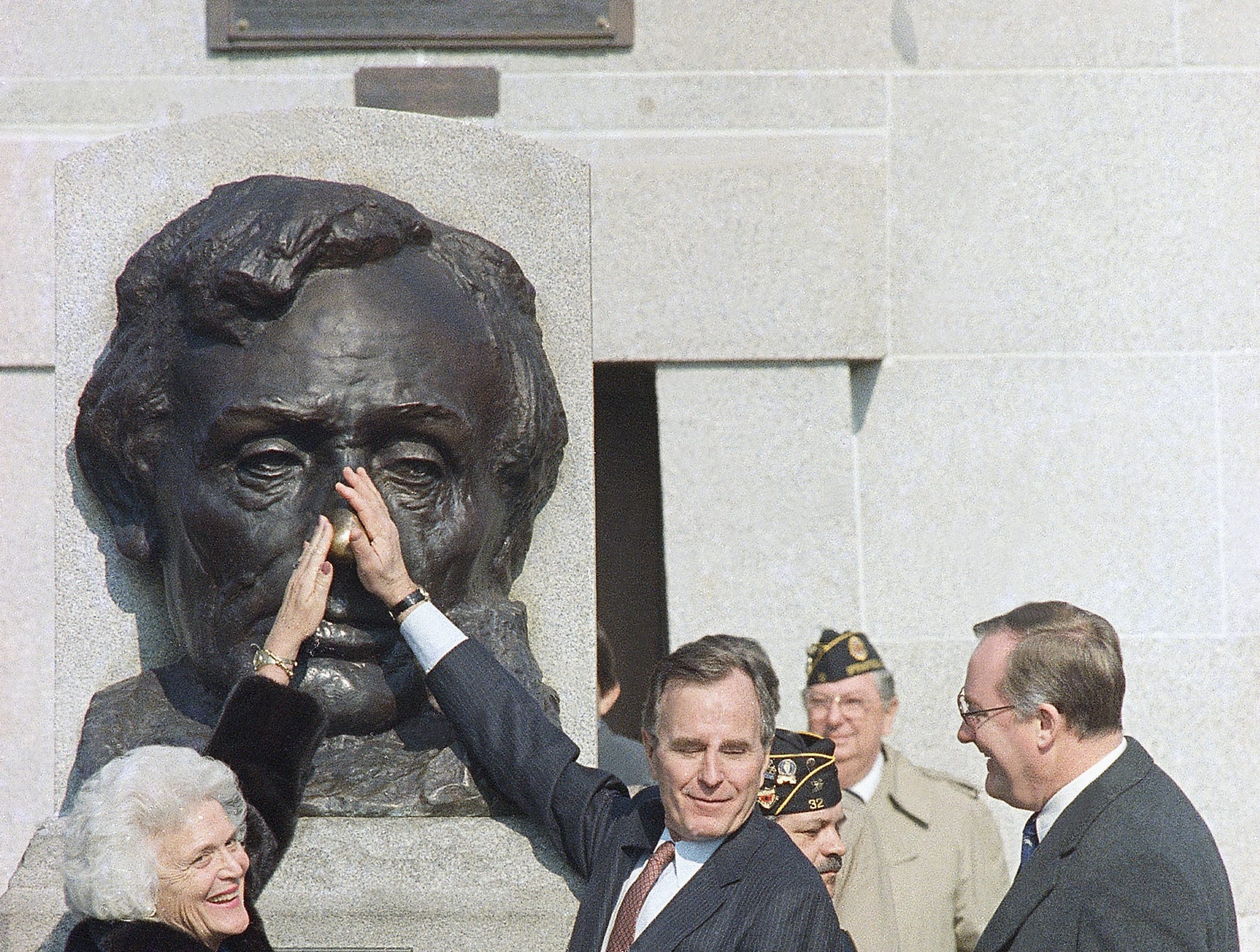 U.S. Vice President George H. Bush, right, and his wife Barbara, left, rubs the nose of the statue of Abraham Lincoln for good luck after participating in wreath-laying ceremonies at Lincoln's Tomb in Springfield, Ill., Feb. 12, 1987.  (AP Photo/Seth Perlman)