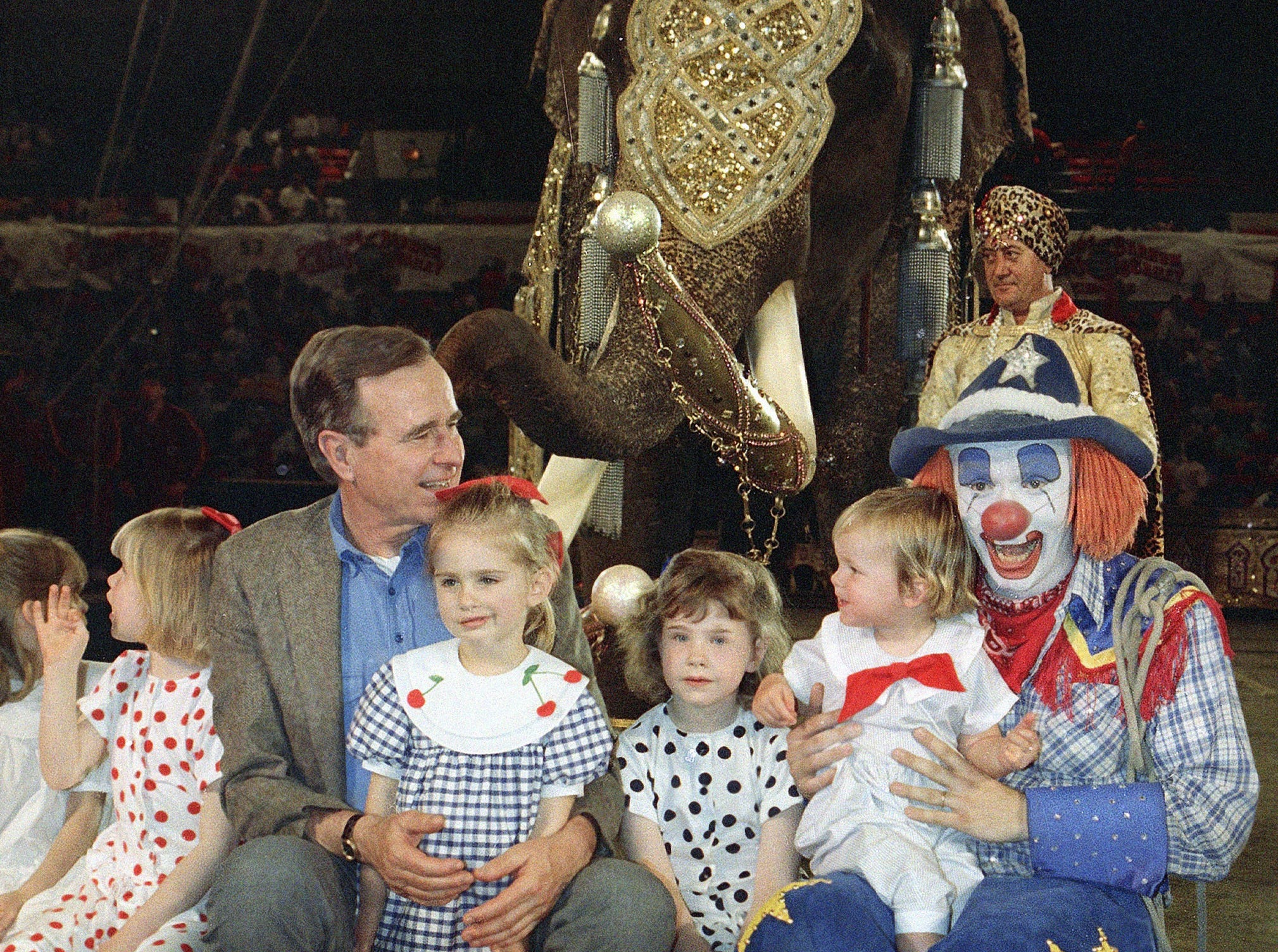 "Vice President George Bush, with the aid of a circus clown, holds some of his grandchildren, prior to a performance of Ringling Brothers and Barnum & Bailey Circus they attended in Washington, April 4, 1988. Behind them is the elephant the circus calls ""King Tusk, the largest land mammal traveling the face of the earth."" (AP Photo/Doug Mills)"