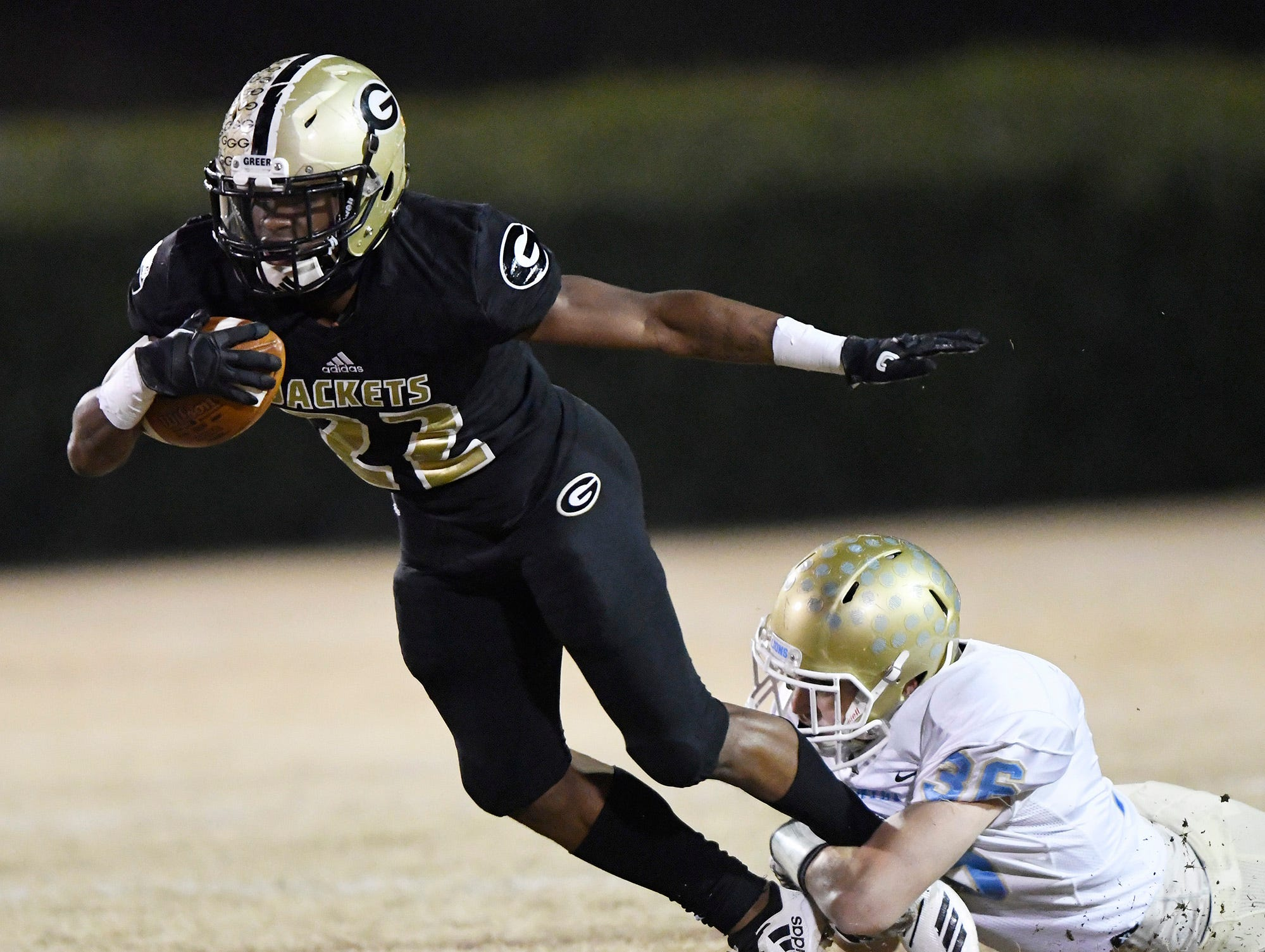 Greer's Dre Williams (22) is slowed by Daniel's David Cote (36) in the class AAAA upstate championship Friday, November 30, 2018 at Greer's Dooley Field.