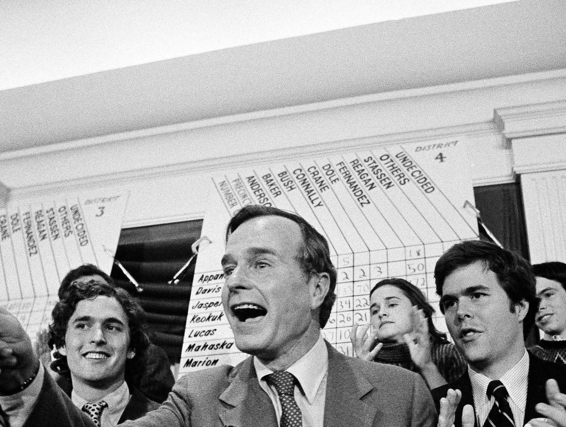 George Bush acknowledges cheers at the Republican caucus headquarters in Des Moines, Iowa on January 22, 1980. Bush took a lead over front-runner Ronald Reagan and seven other candidates for the Republican presidential nomination, in the Iowa Republican straw-poll caucus. At far right is Bush's son Jeb. (AP Photo/Jim Mone)