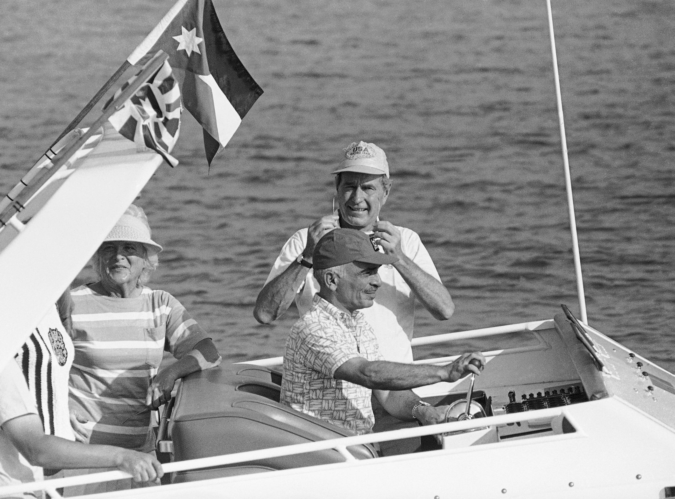 With King Hussein of Jordan, at the helm, Vice President George H.W. Bush, standing, center, and their wives, Barbara Bush, and Queen Noor, blocked on left, cruise while staying at the king's summer guest house, Aug. 1, 1986, Aqaba, Jordan. (AP Photo/ Ron Edmonds)