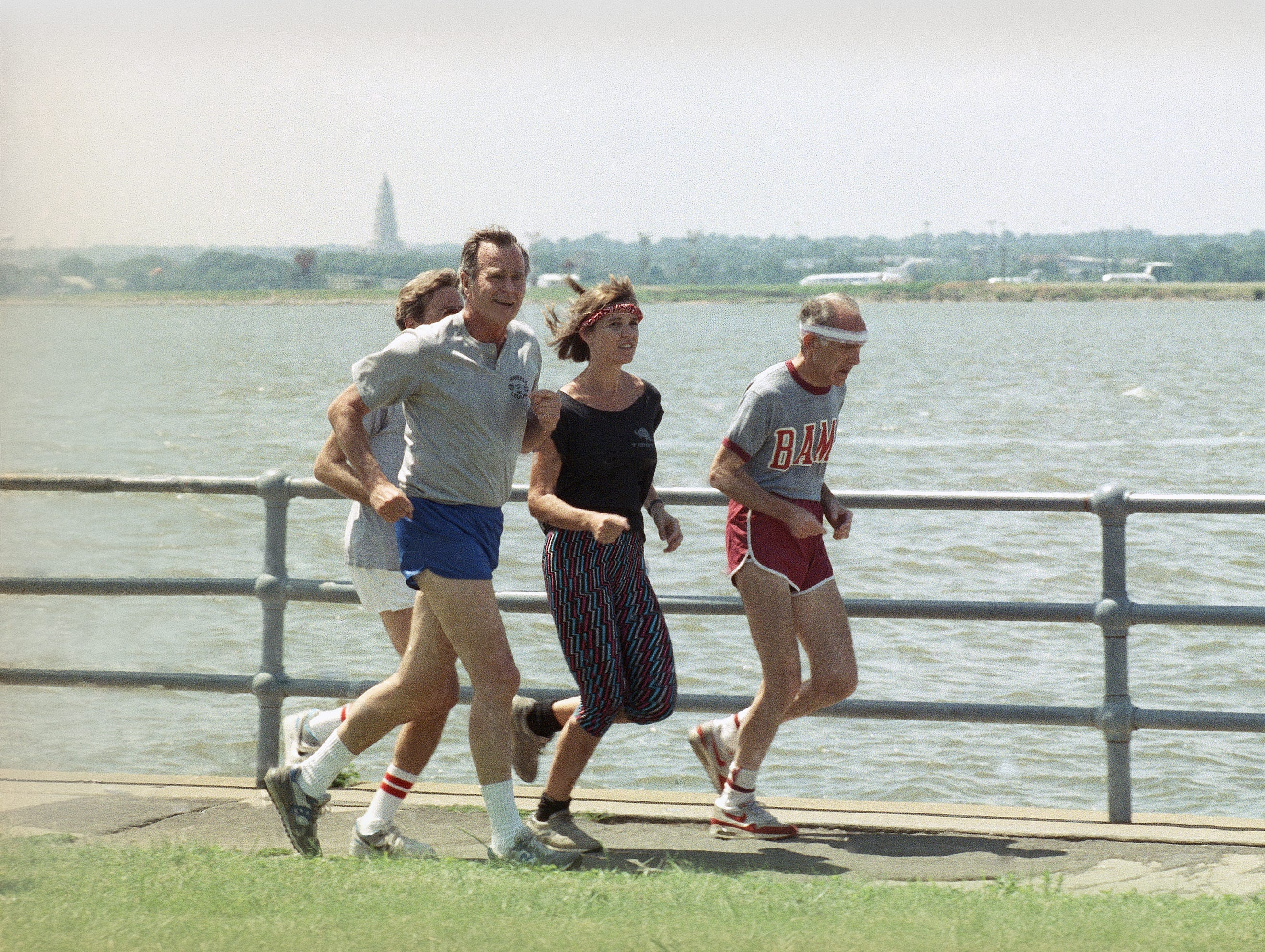 President George H. Bush goes jogging with reporters Norm Sandler, left, Rita Beamish, and personal friend Vic Gold, right, Tuesday, August 8, 1989, in a Washington park along the Potomac River. (AP Photo/Barry Thumma)