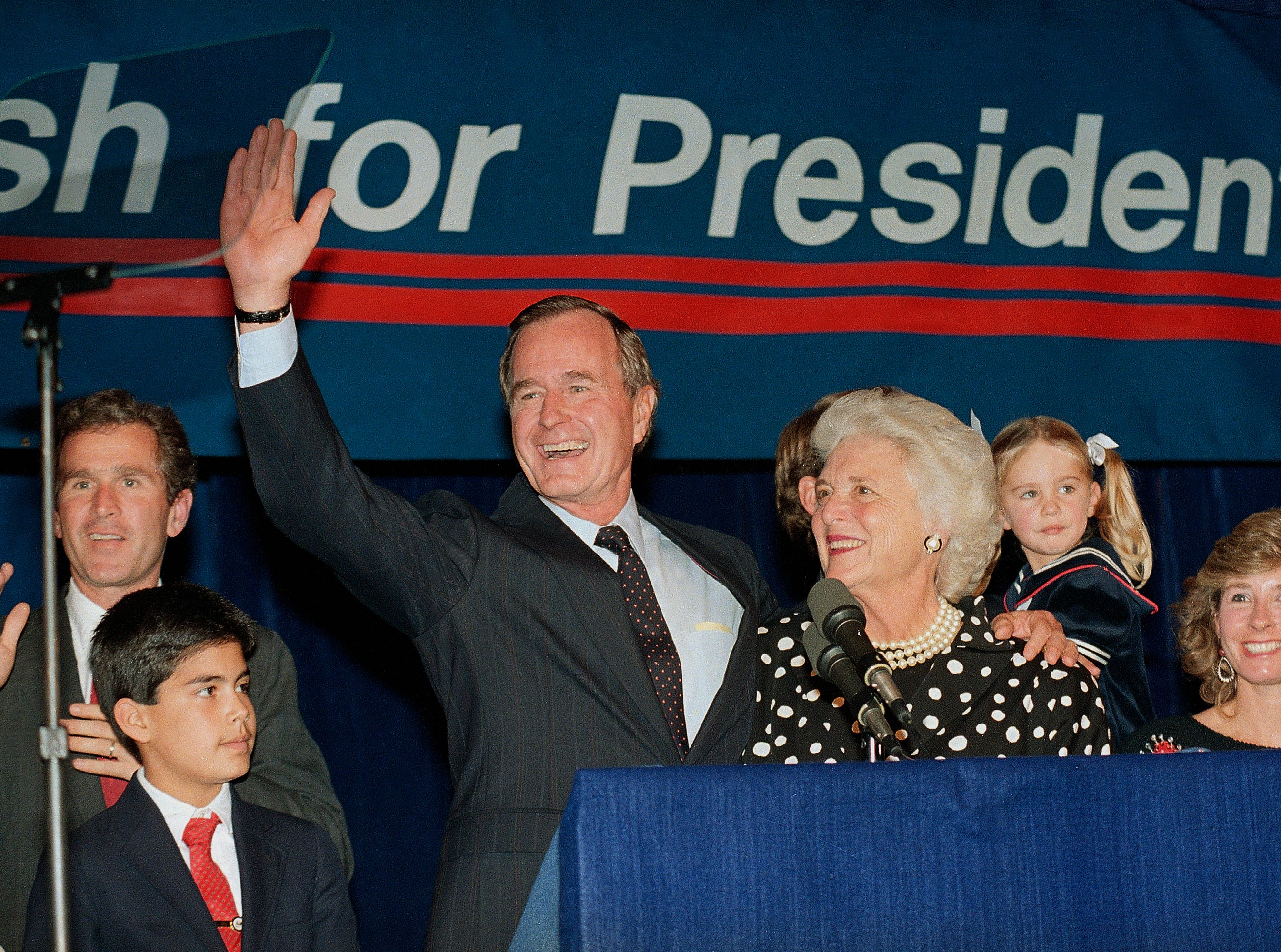 In this Oct. 12, 1987, file photo, Vice President George H.W. Bush and his wife, Barbara, with their son George W. Bush, far left, wave to supporters who turned out in Houston to hear him announce he was a candidate for the Republican nomination for president of the United States.